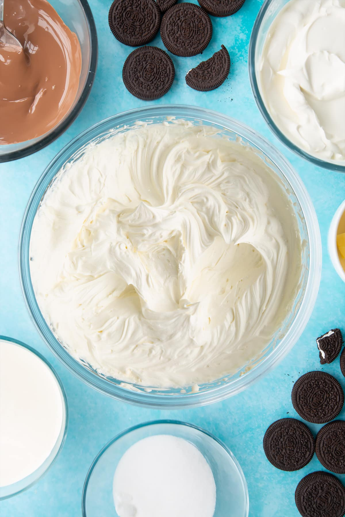 Overhead shot of whipped cream, cream, sugar and cream cheese mixed together in a large clear bowl