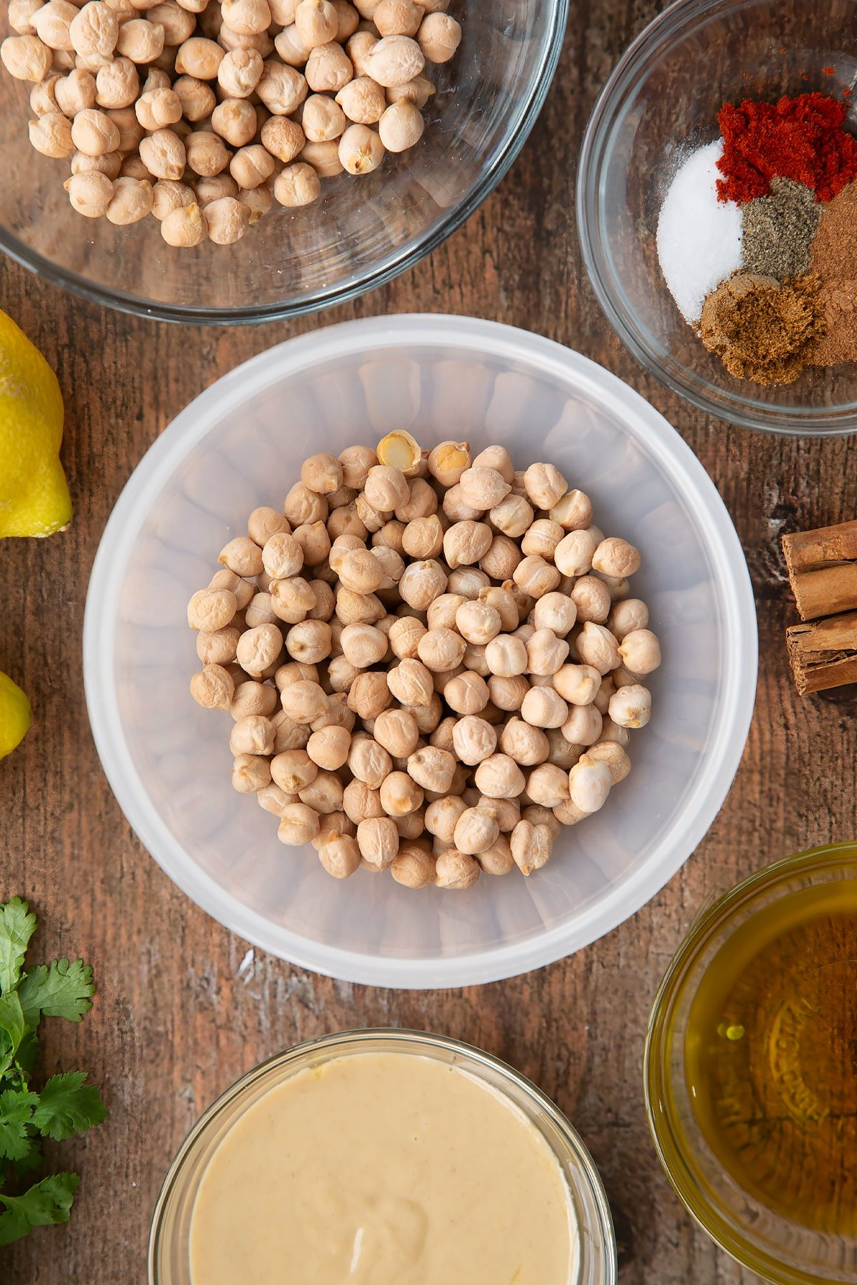 Dried chickpeas in a plastic bowl. Ingredients to make cinnamon hummus surround the bowl.