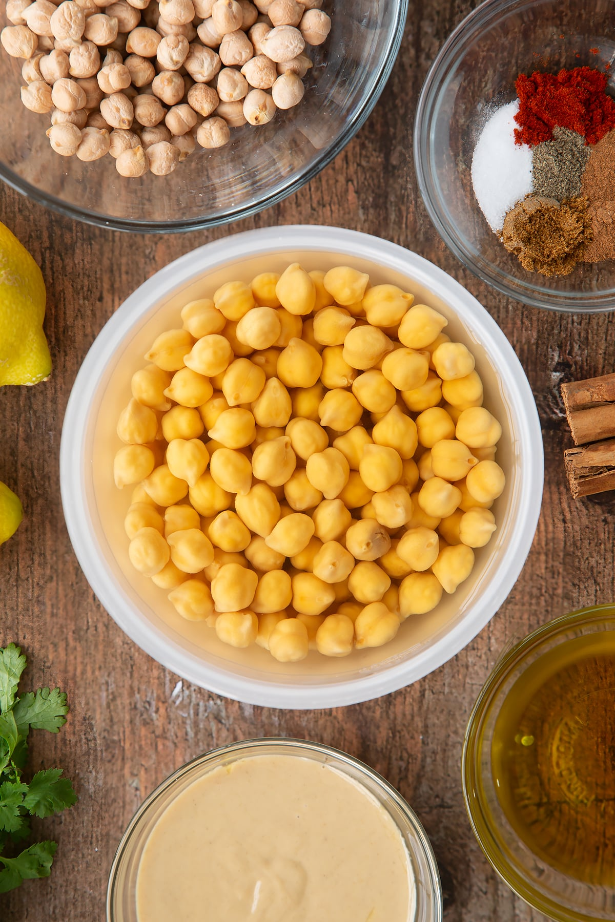 Soaked chickpeas in water in a plastic bowl. Ingredients to make cinnamon hummus surround the bowl.