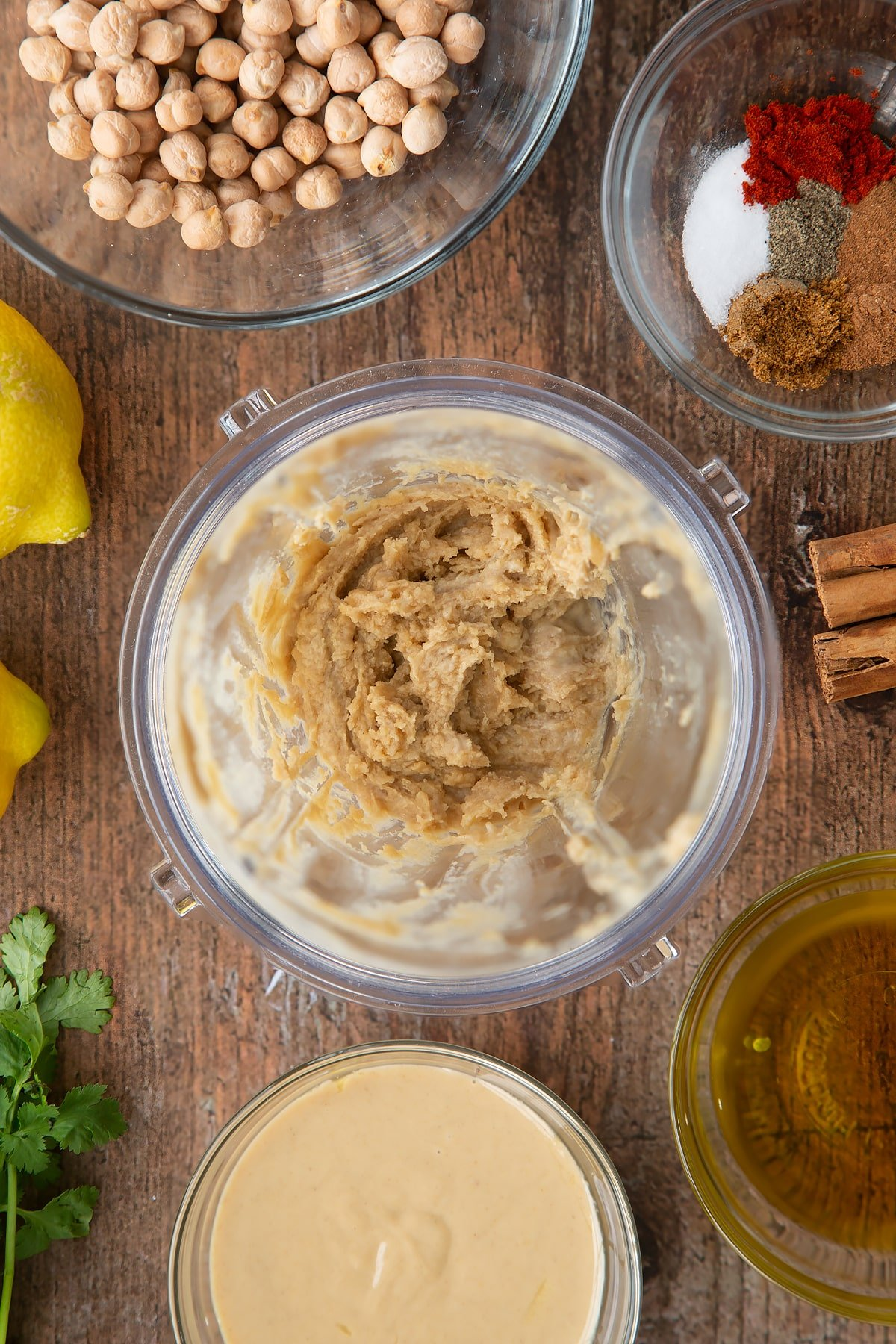 Tahini and lemon juice whipped in a small blender bowl. Ingredients to make cinnamon hummus surround the bowl.