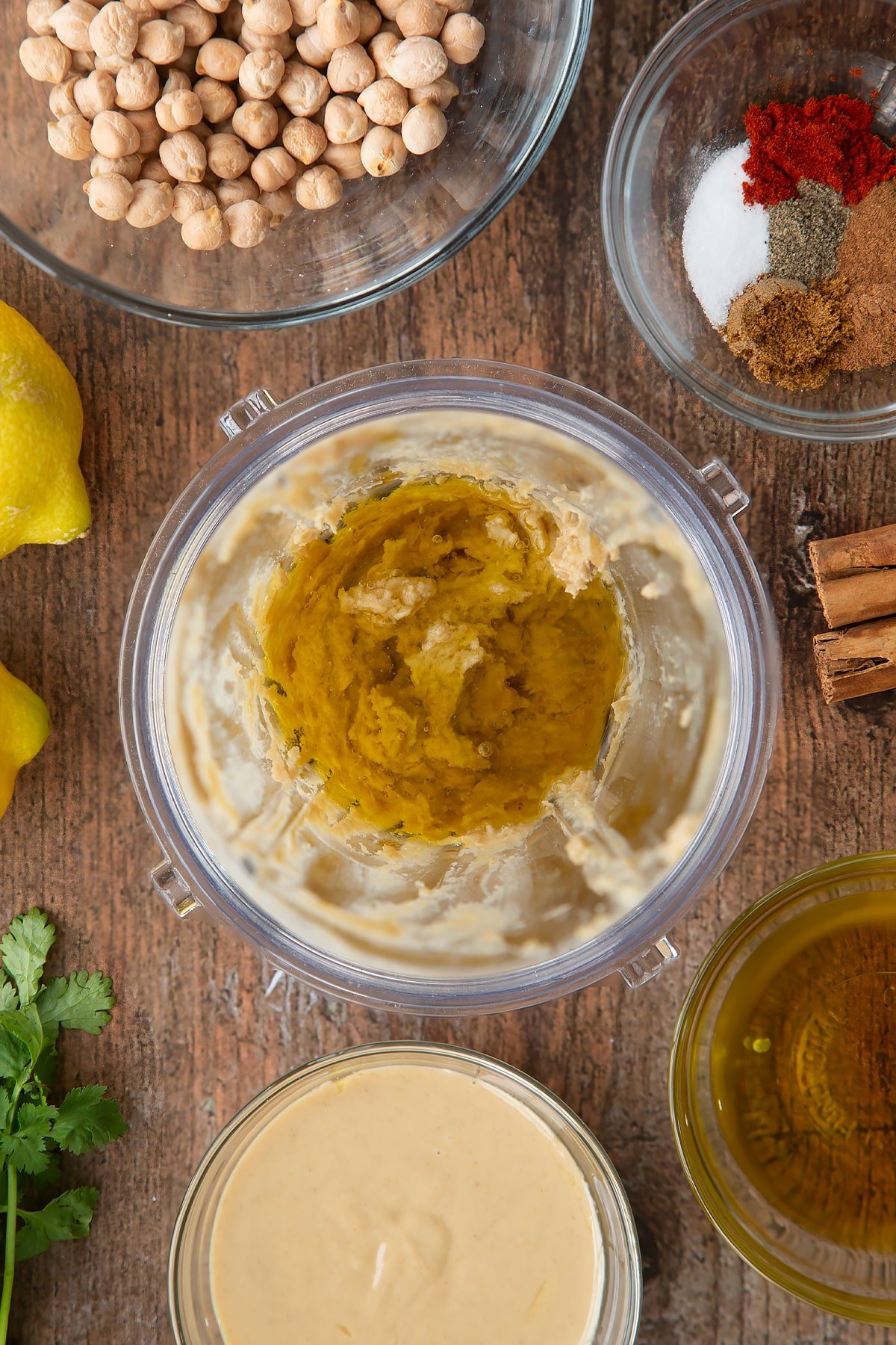 Tahini, lemon juice and oil in a small blender bowl. Ingredients to make cinnamon hummus surround the bowl.
