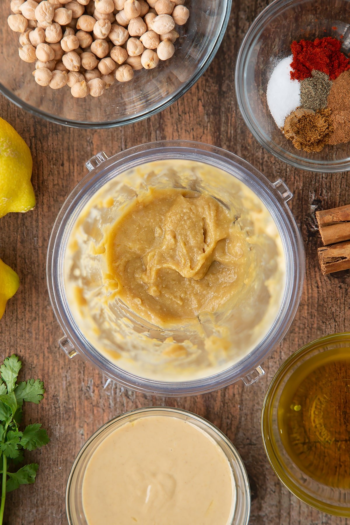 Tahini, lemon juice and oil whipped together in a small blender bowl. Ingredients to make cinnamon hummus surround the bowl.