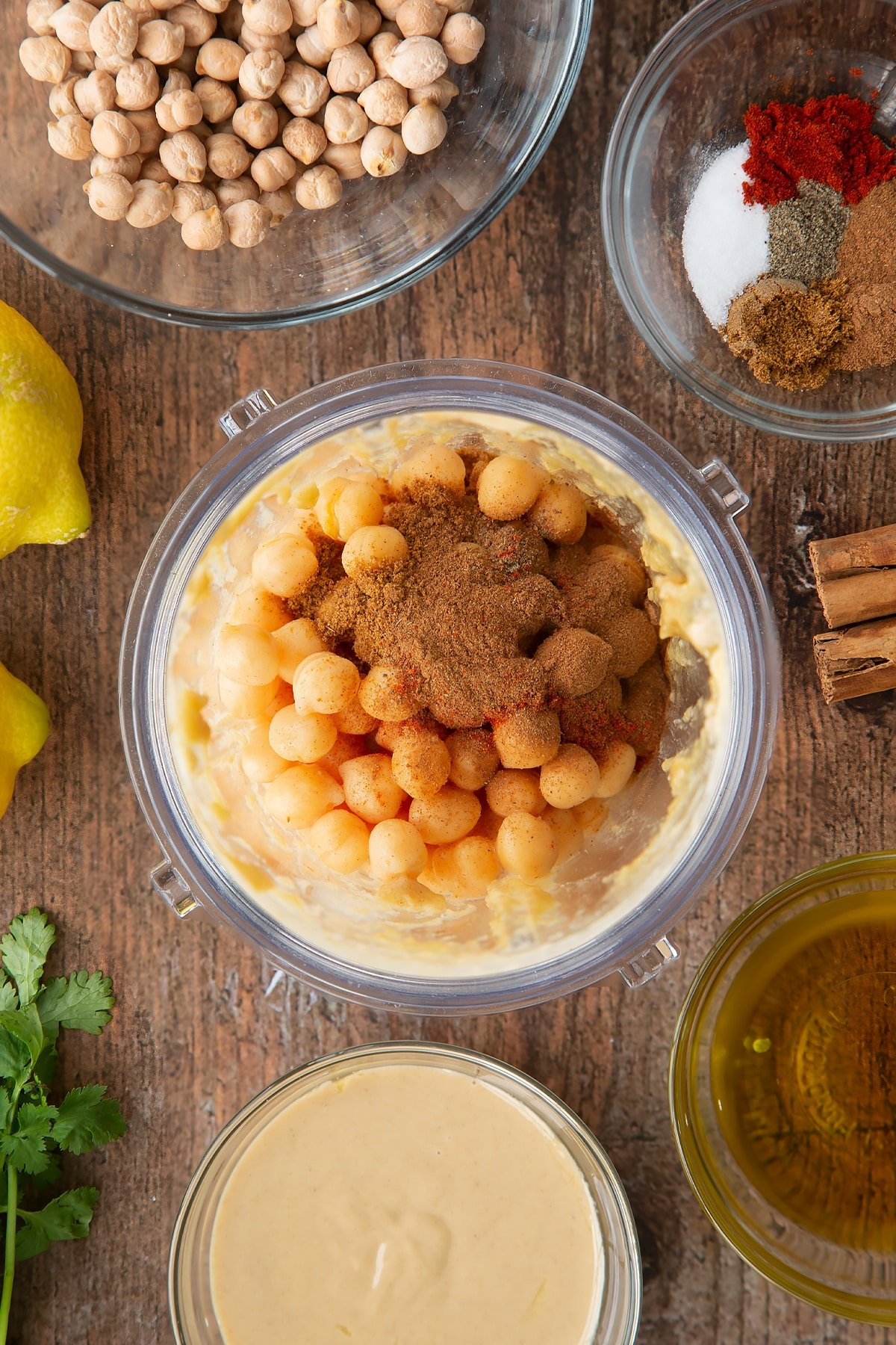 Tahini, lemon juice and oil whipped together in a small blender bowl with cooked chickpeas and spices on top. Ingredients to make cinnamon hummus surround the bowl.