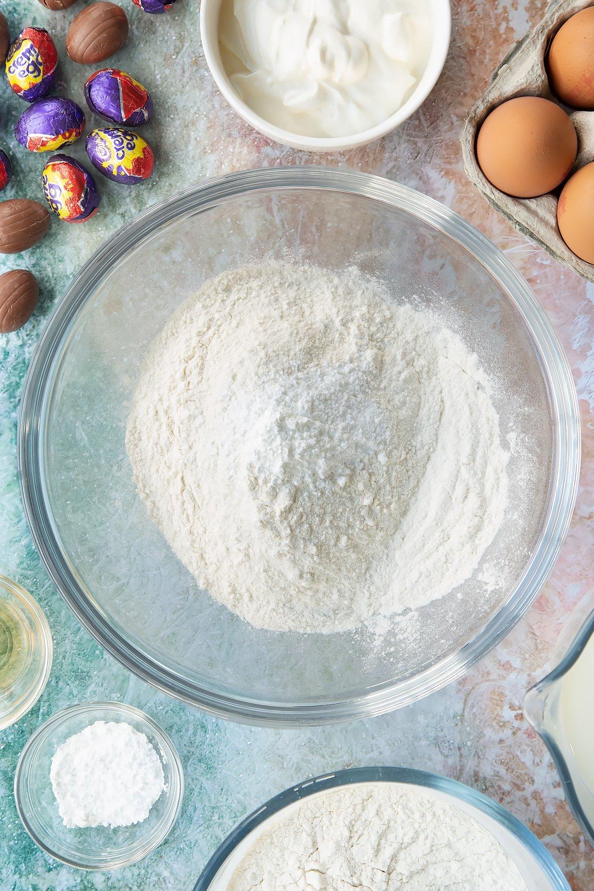 Self-raising flour and baking powder in a bowl. Ingredients to make Creme Egg pancakes surround the bowl.