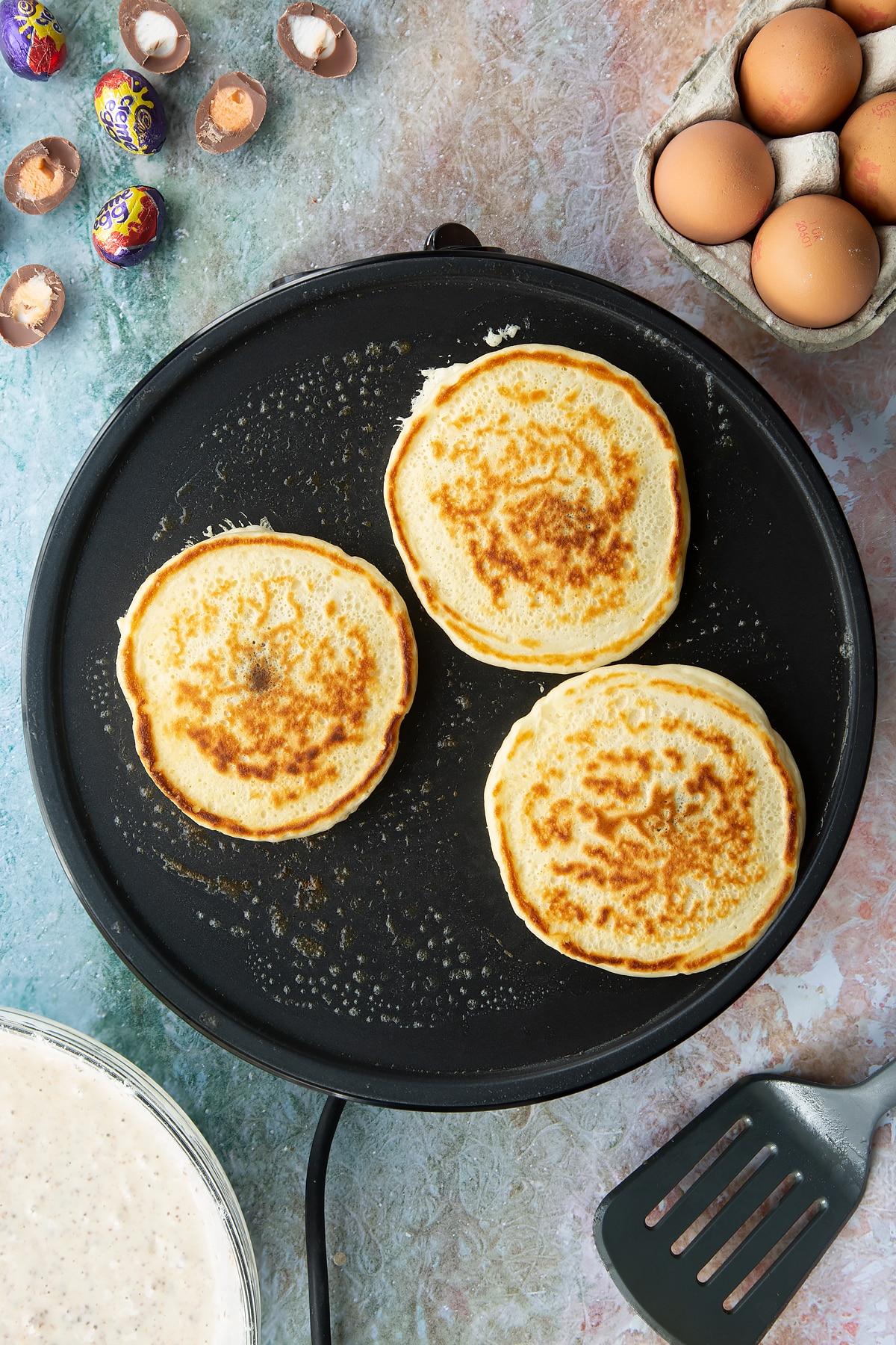 A hot pan with Creme Egg pancakes cooking. Ingredients to make Creme Egg pancakes surround the pan.