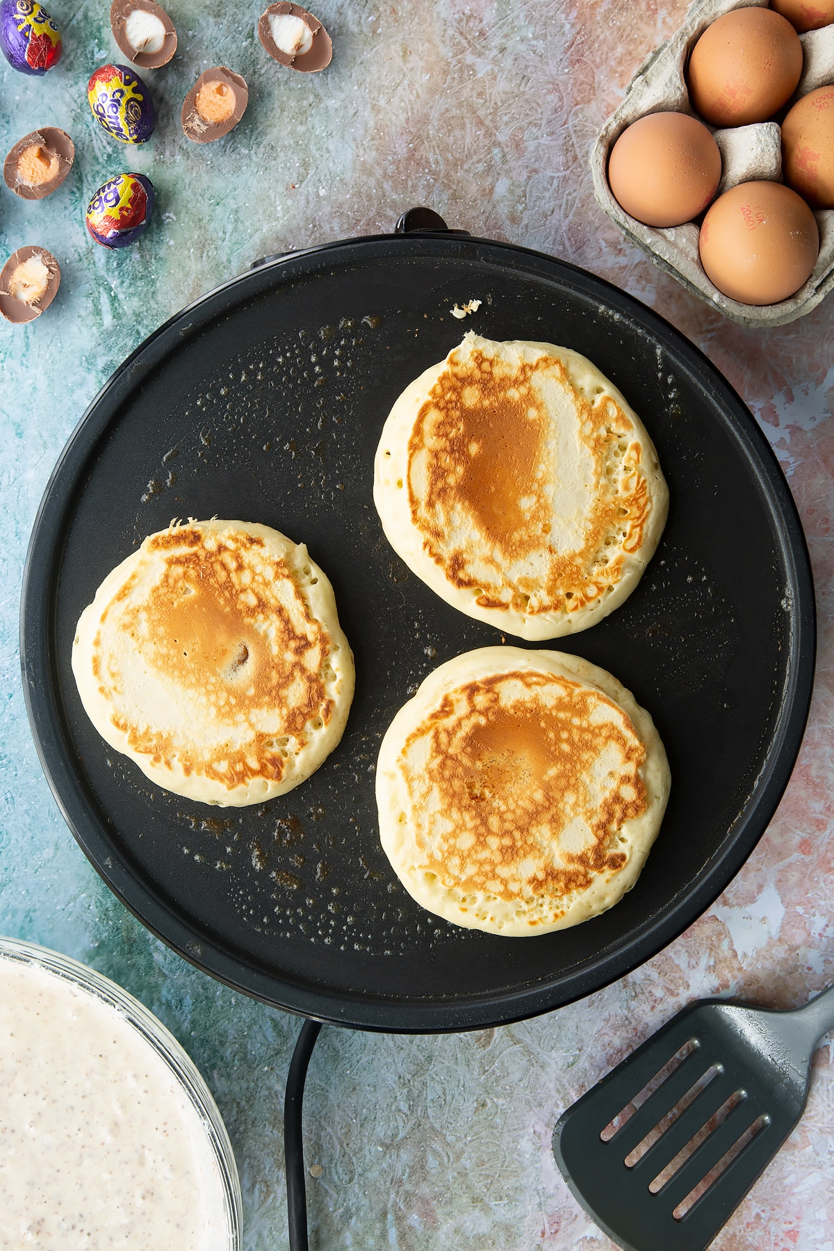 A hot pan with Creme Egg pancakes fully cooked. Ingredients to make Creme Egg pancakes surround the pan.