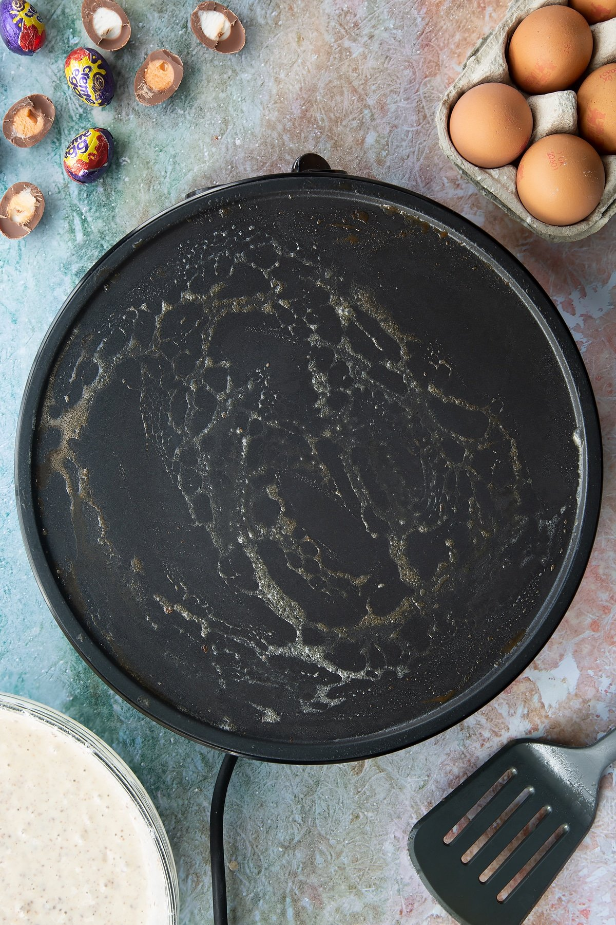 A hot pan with melted butter. Ingredients to make Creme Egg pancakes surround the pan.