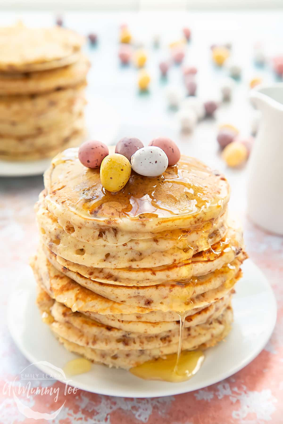 Thick, fluffy Mini Egg pancakes on a white plate in a tall stack. They are drizzled with syrup and topped with Mini Eggs.
