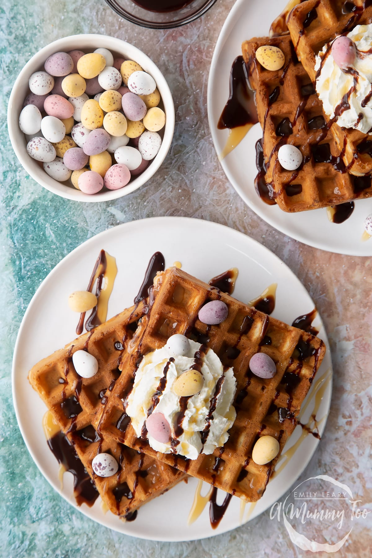 Mini egg waffles shown from above on white plates. They are topped with squirty cream, chocolate sauce, toffee sauce and Mini Eggs.