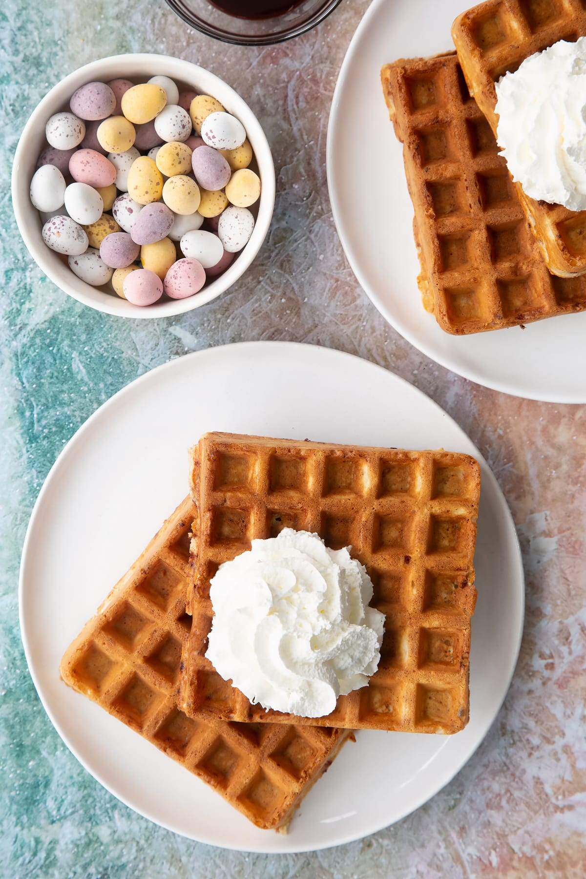 Mini egg waffles on a white plate. They are topped with squirty cream.