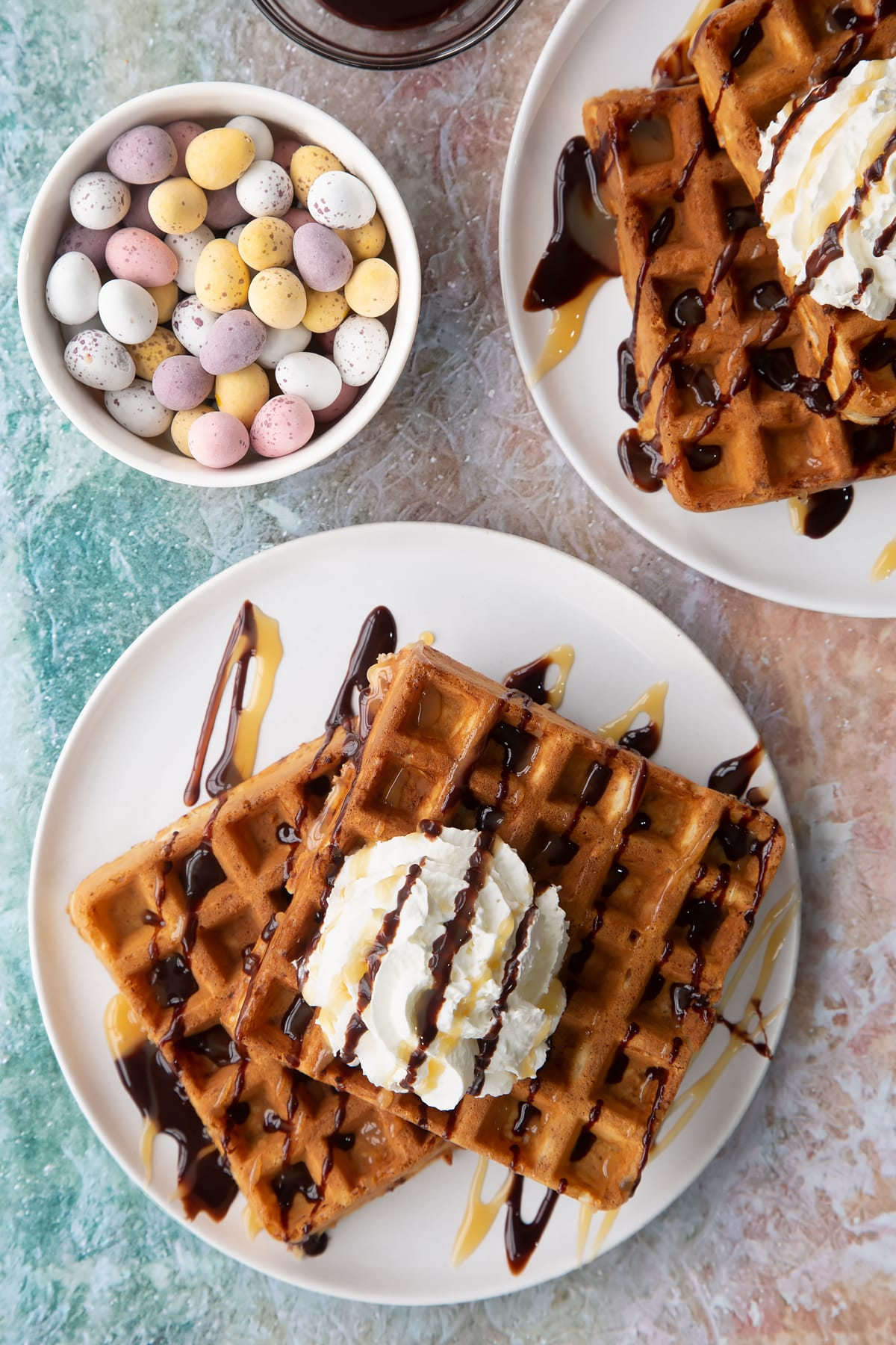 Mini egg waffles on a white plate. They are topped with squirty cream, chocolate sauce and toffee sauce.