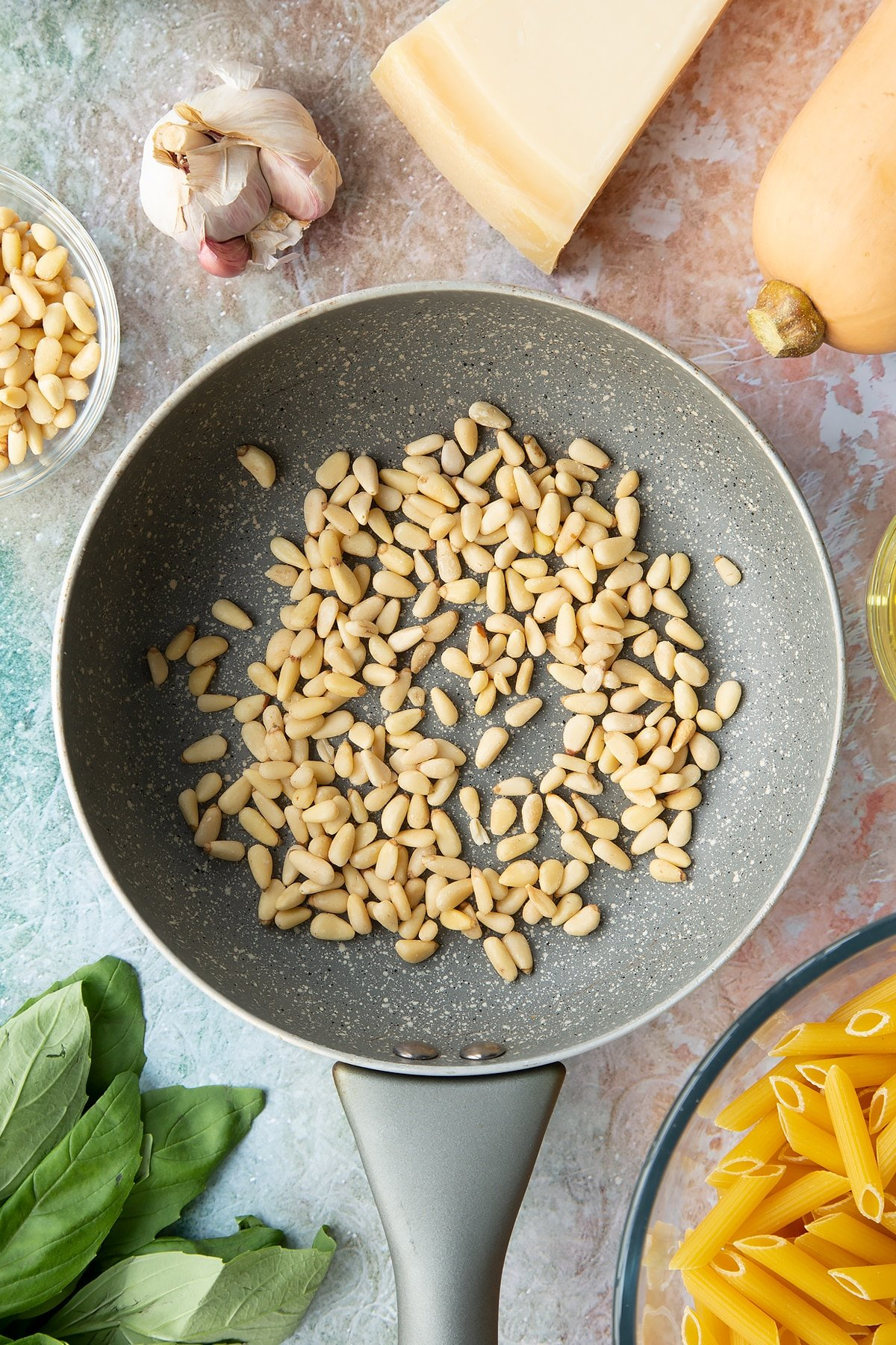 Pine nuts in a small frying pan. Ingredients to make penne with butternut squash and goat cheese surround the pan.