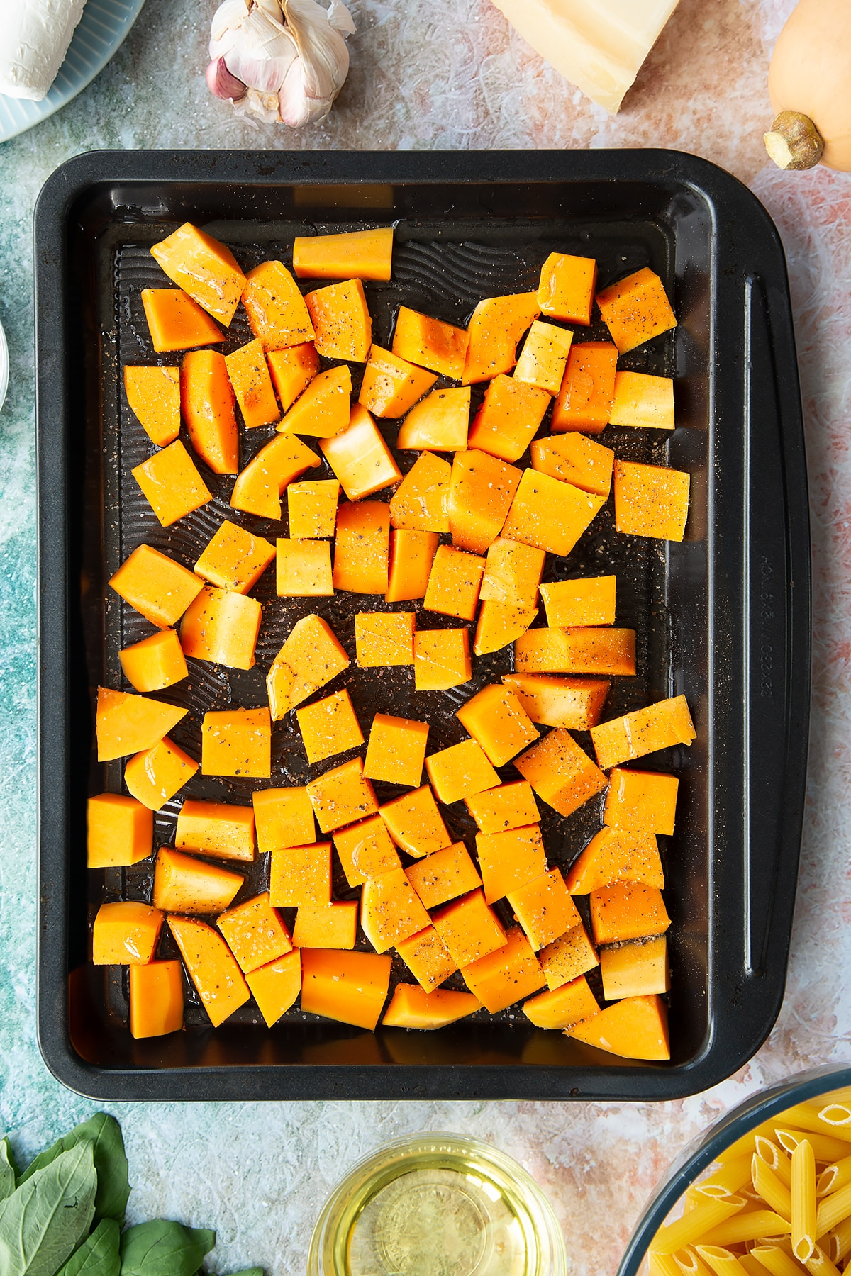 Chunks of butternut squash on a black tray, seasoned with oil, salt and pepper. Ingredients to make penne with butternut squash and goat cheese surround the tray.
