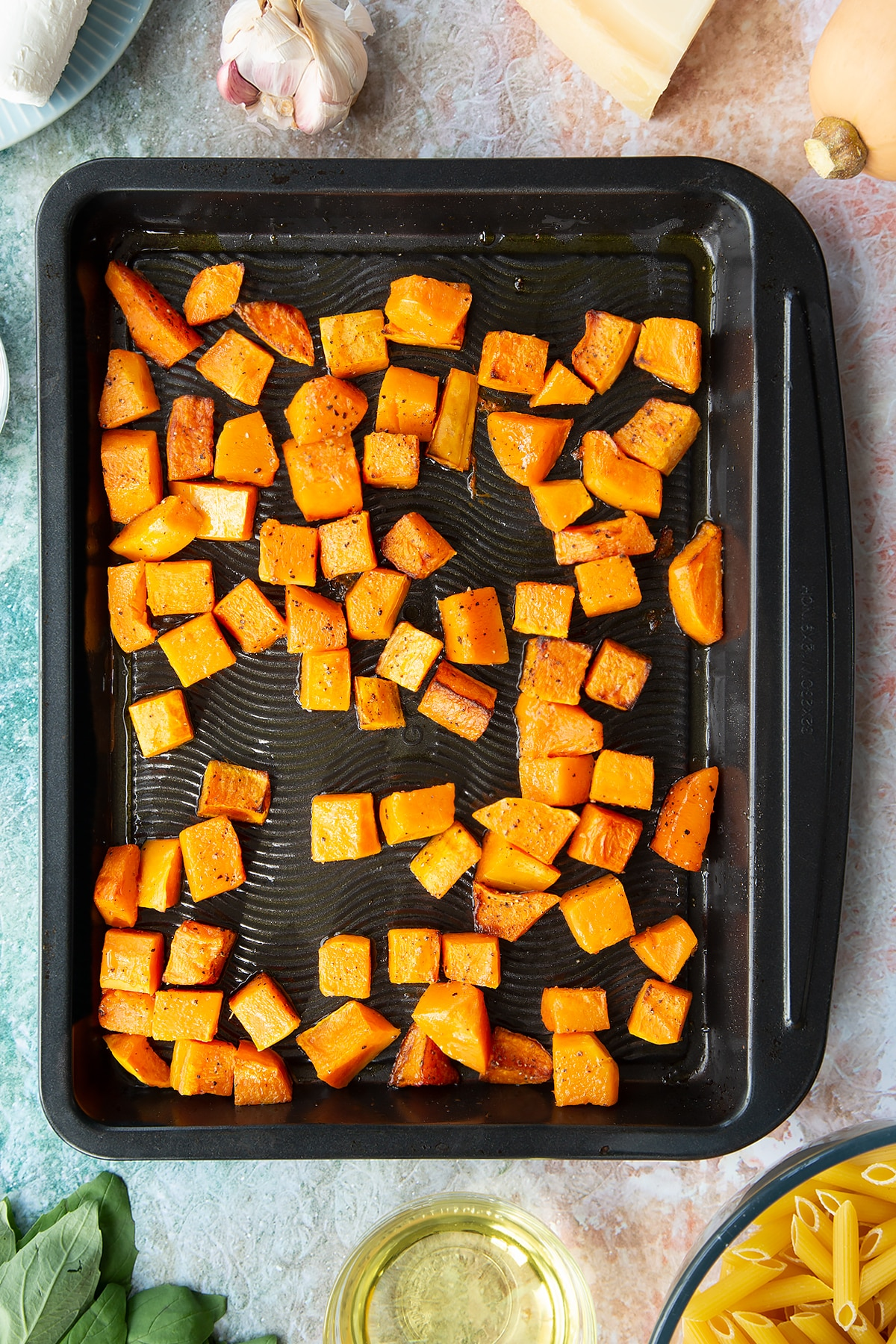 Roasted chunks of butternut squash on a black tray. Ingredients to make penne with butternut squash and goat cheese surround the tray.
