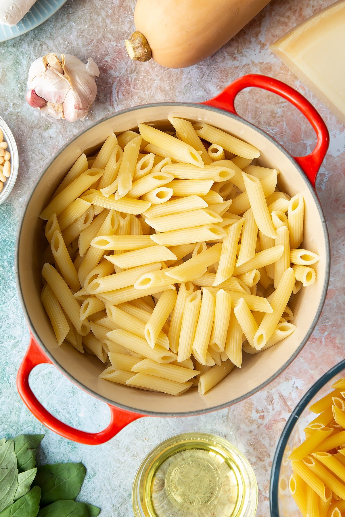 Cooked and drained penne pasta in a pan. Ingredients to make penne with butternut squash and goat cheese surround the pan.