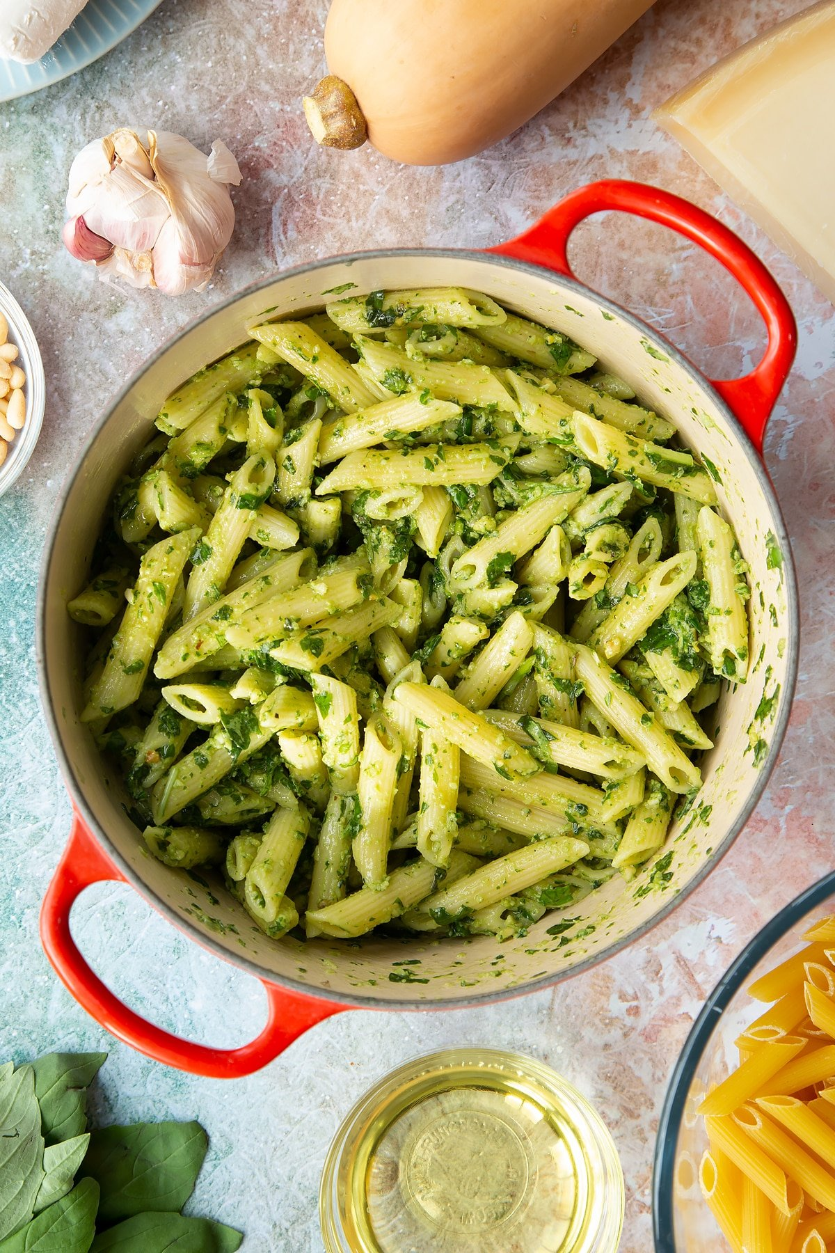 Penne pasta tossed with fresh pesto in a pan. Ingredients to make penne with butternut squash and goat cheese surround the pan.