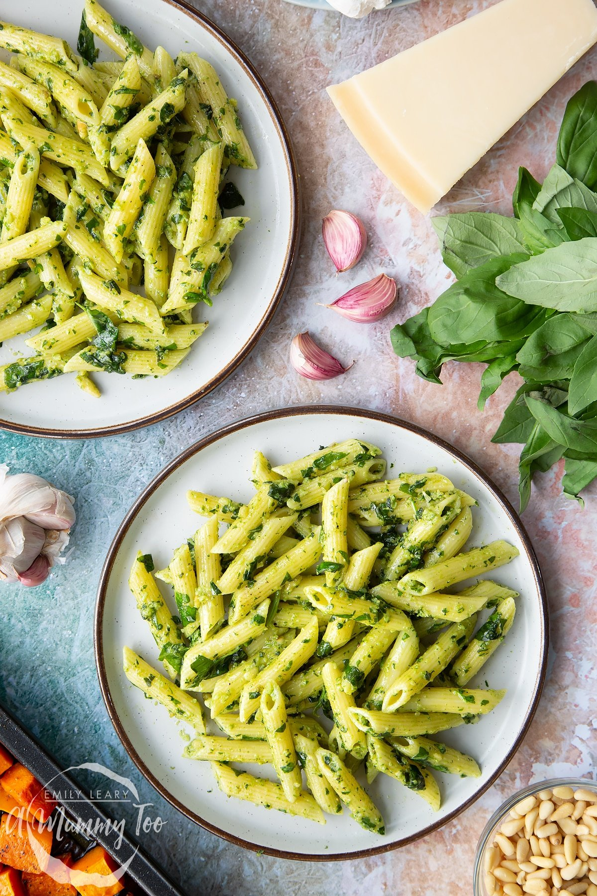 Penne pasta tossed with fresh pesto served to plates. Ingredients to make penne with butternut squash and goat cheese surround the plates.