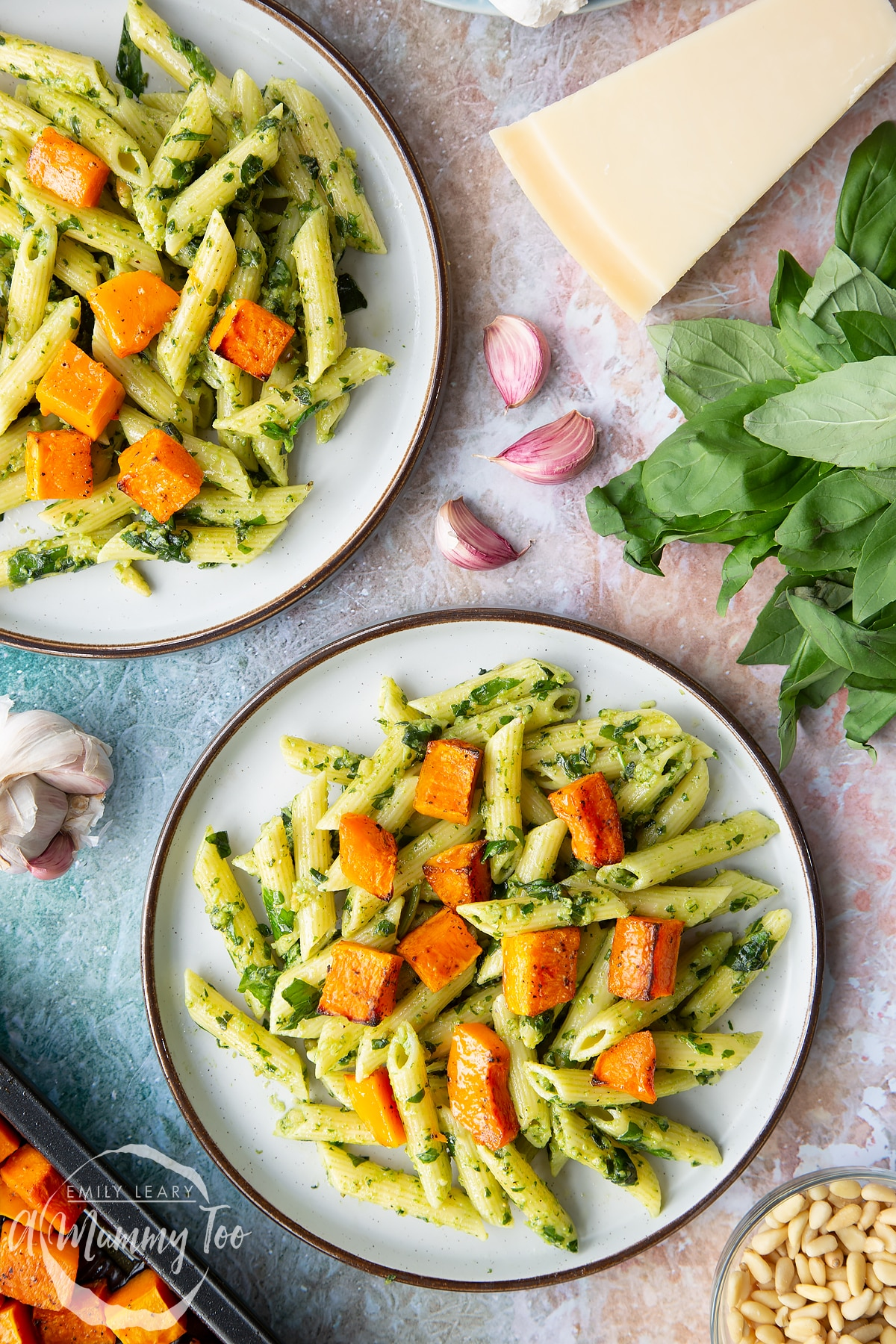 Penne pasta tossed with fresh pesto, served to plates and topped with roasted butternut squash. Ingredients to make penne with butternut squash and goat cheese surround the plates.