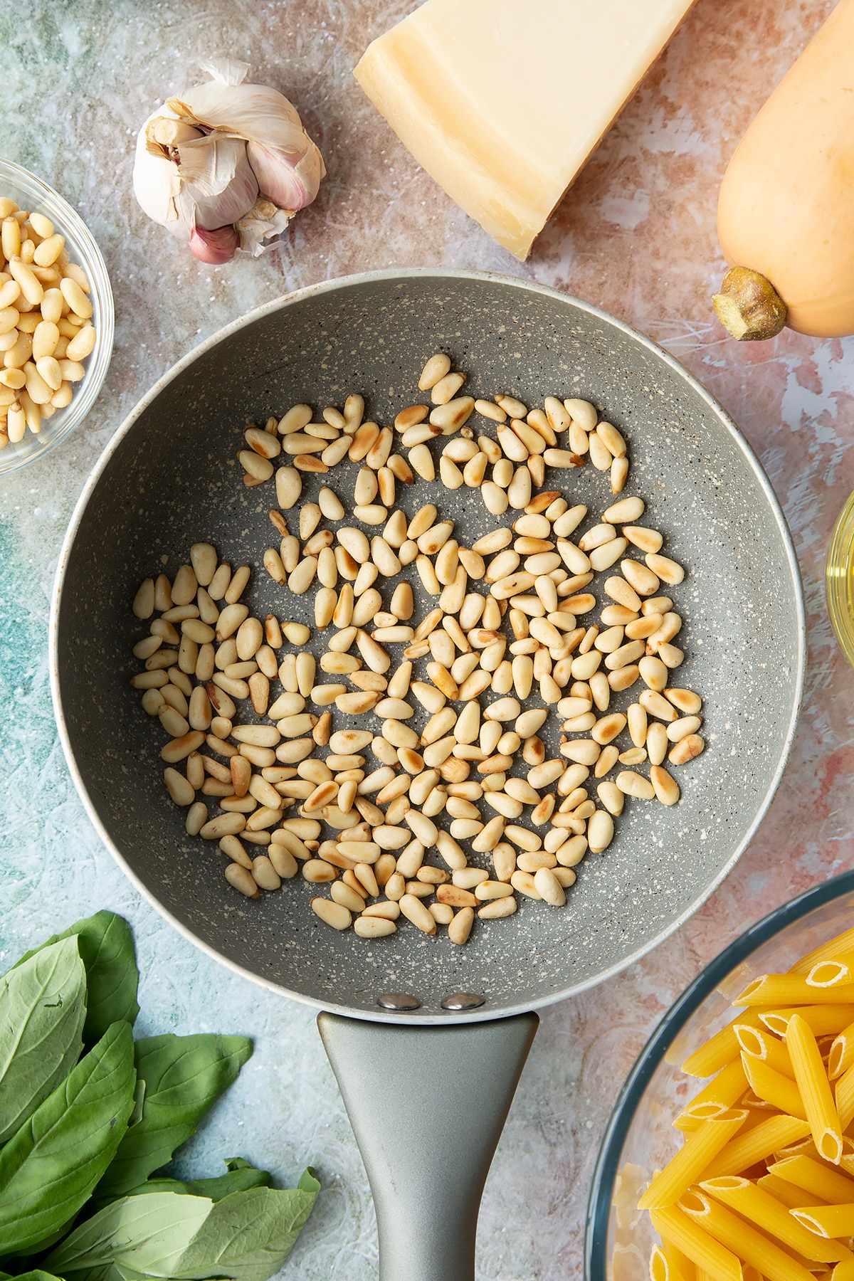 Toasted pine nuts in a small frying pan. Ingredients to make penne with butternut squash and goat cheese surround the pan.