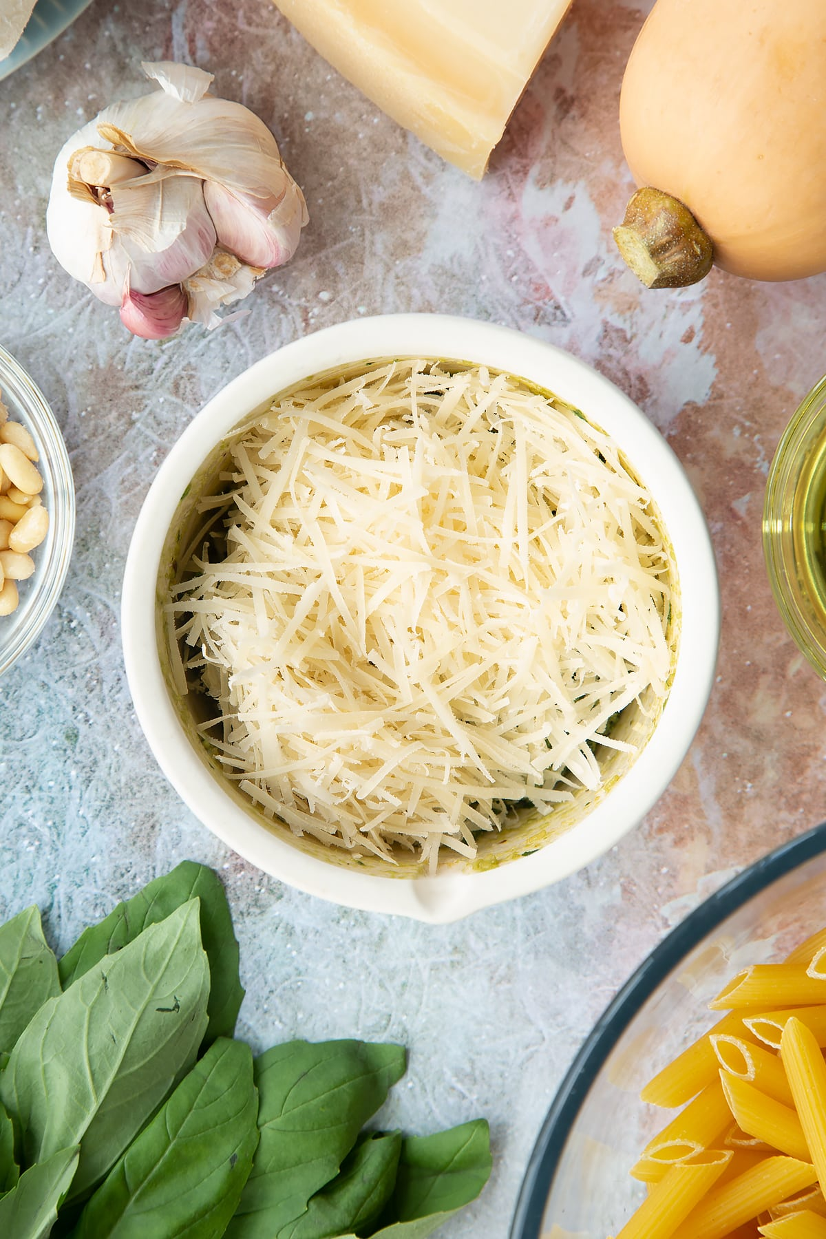 Toasted pine nuts, garlic, pepper and basil crushed in a small mortar with oil and Parmesan on top. Ingredients to make penne with butternut squash and goat cheese surround the mortar.