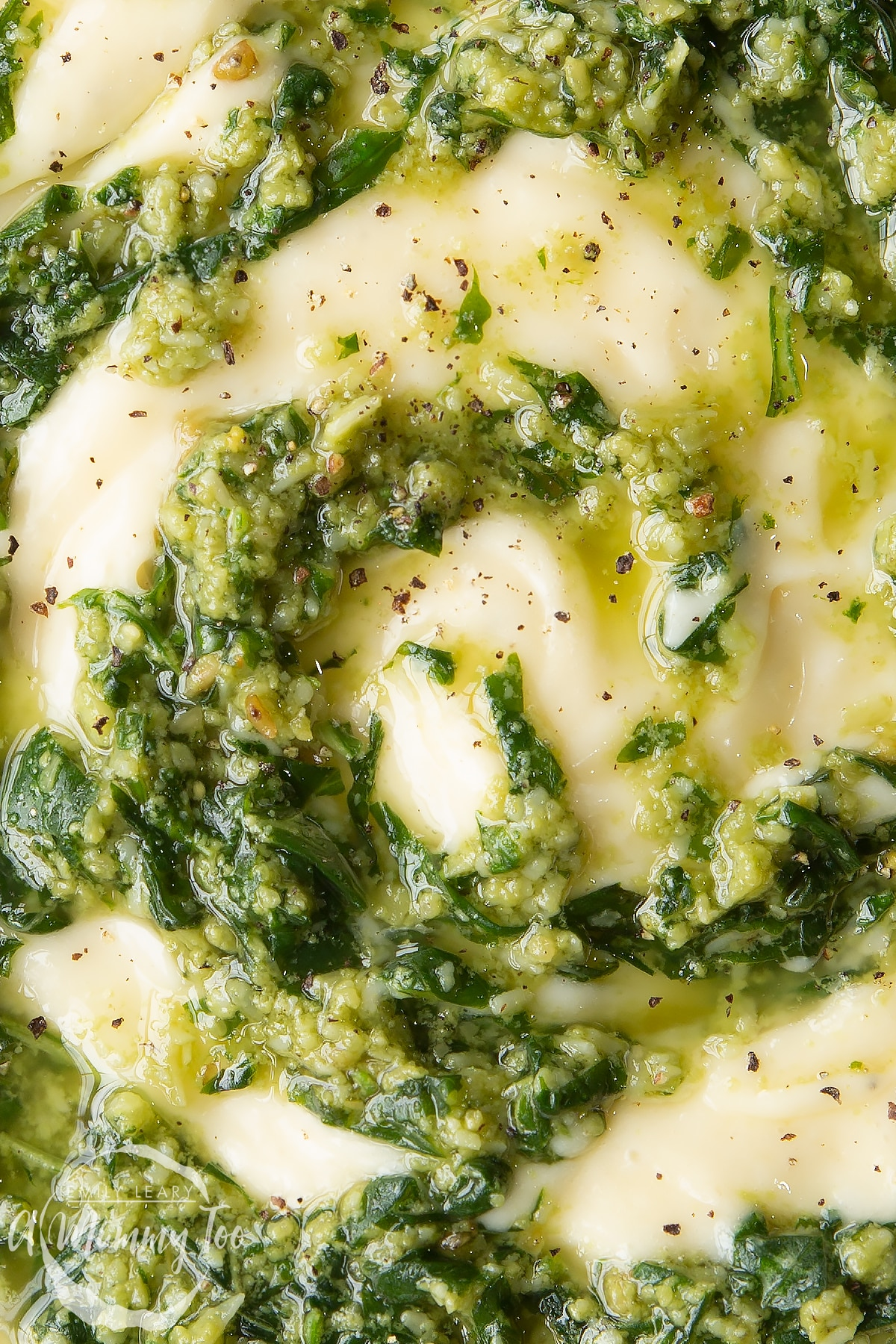 Close up of pesto mayo from above. The pesto and mayonnaise are swirled together.