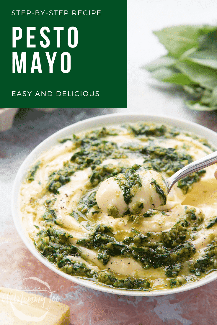 Pesto mayo in a white bowl. The pesto and mayonnaise are swirled together. A hand holds a spoonful above the bowl. Caption: step-by-step recipe pesto mayo easy and delicious