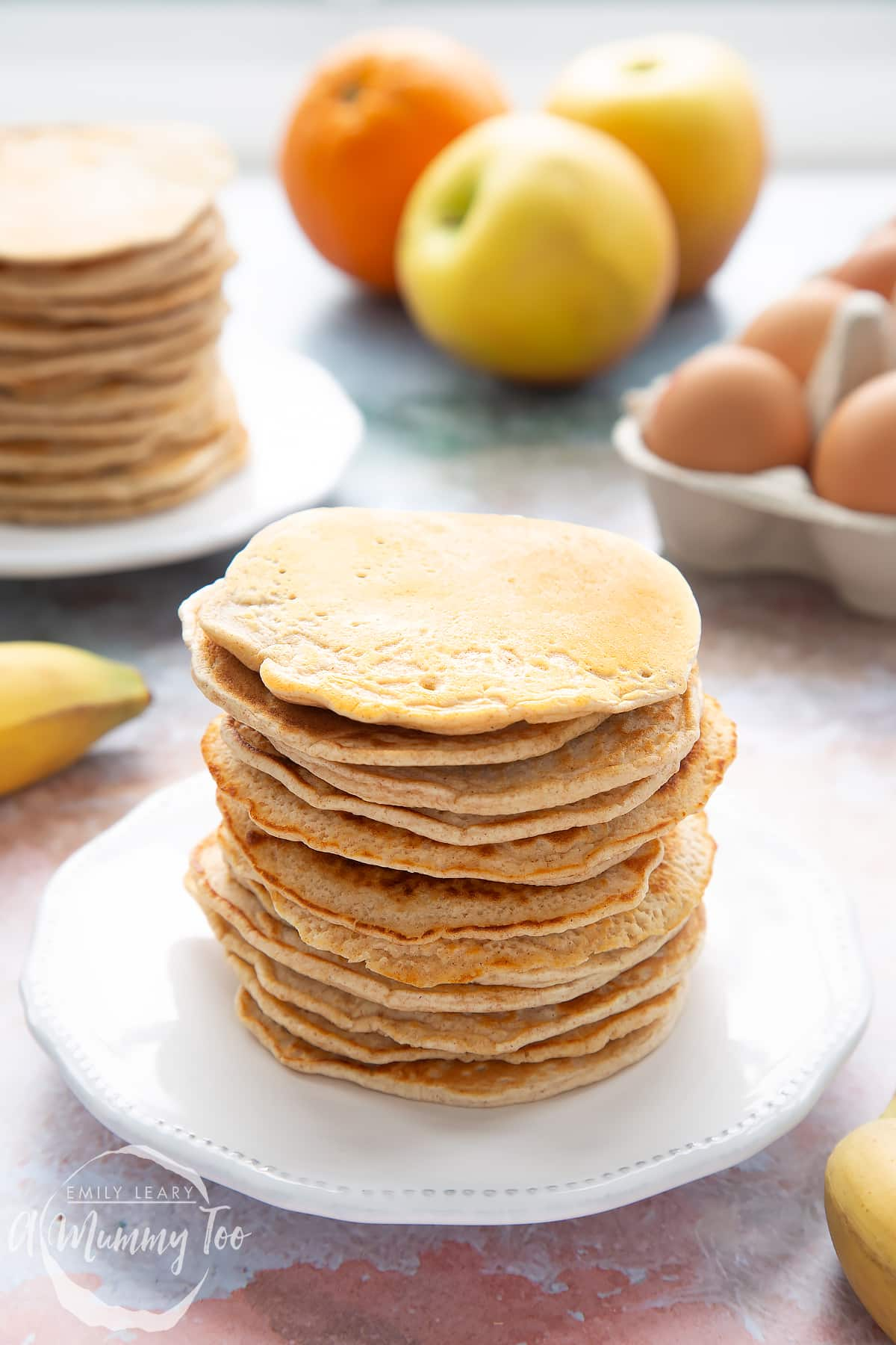 Overhead shot of a pancake stack on a white plate with the A Mummy Too logo in the corner
