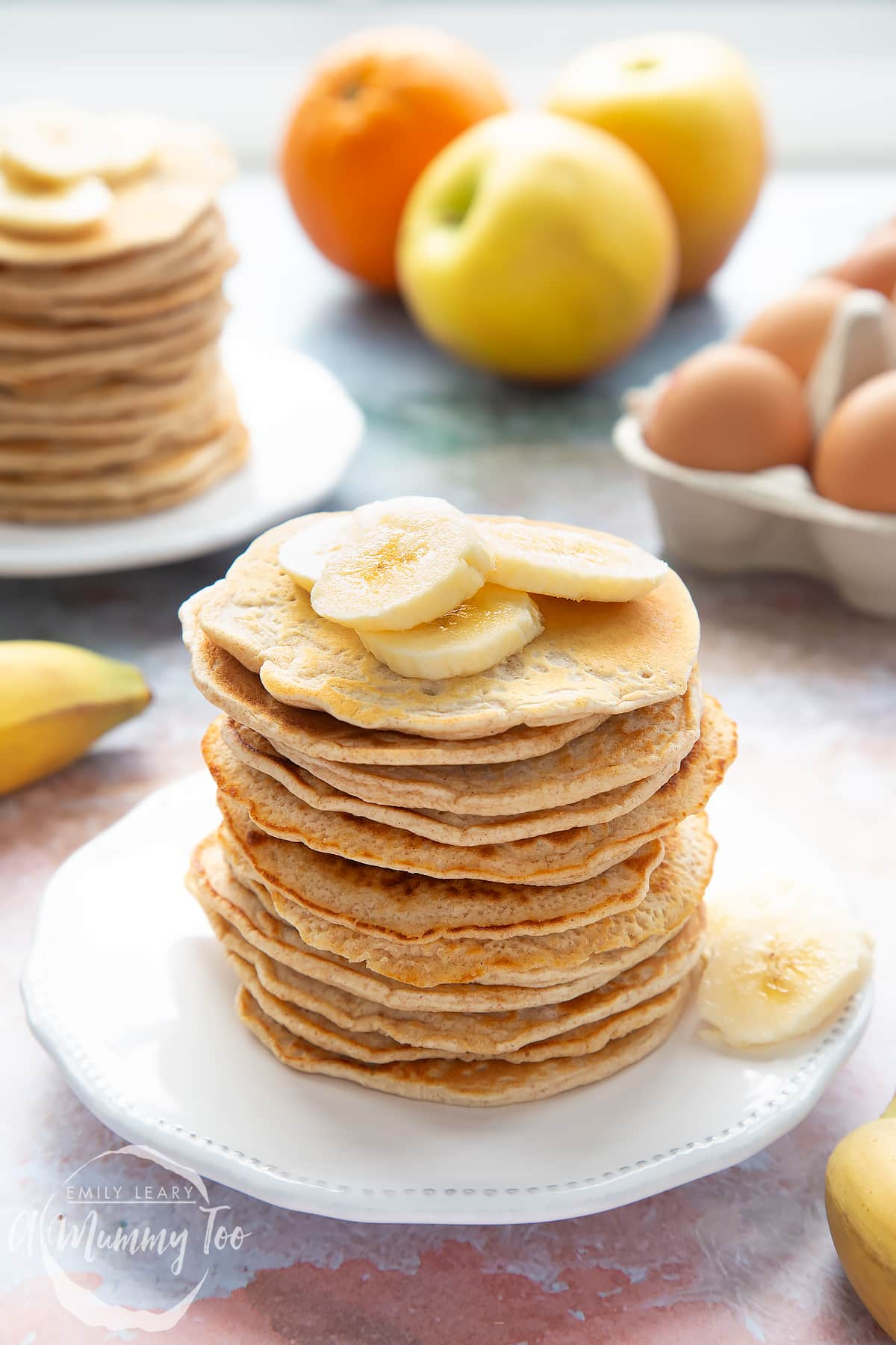 Overhead shot of a pancake stack on a white plate topped with banana with the A Mummy Too logo in the corner