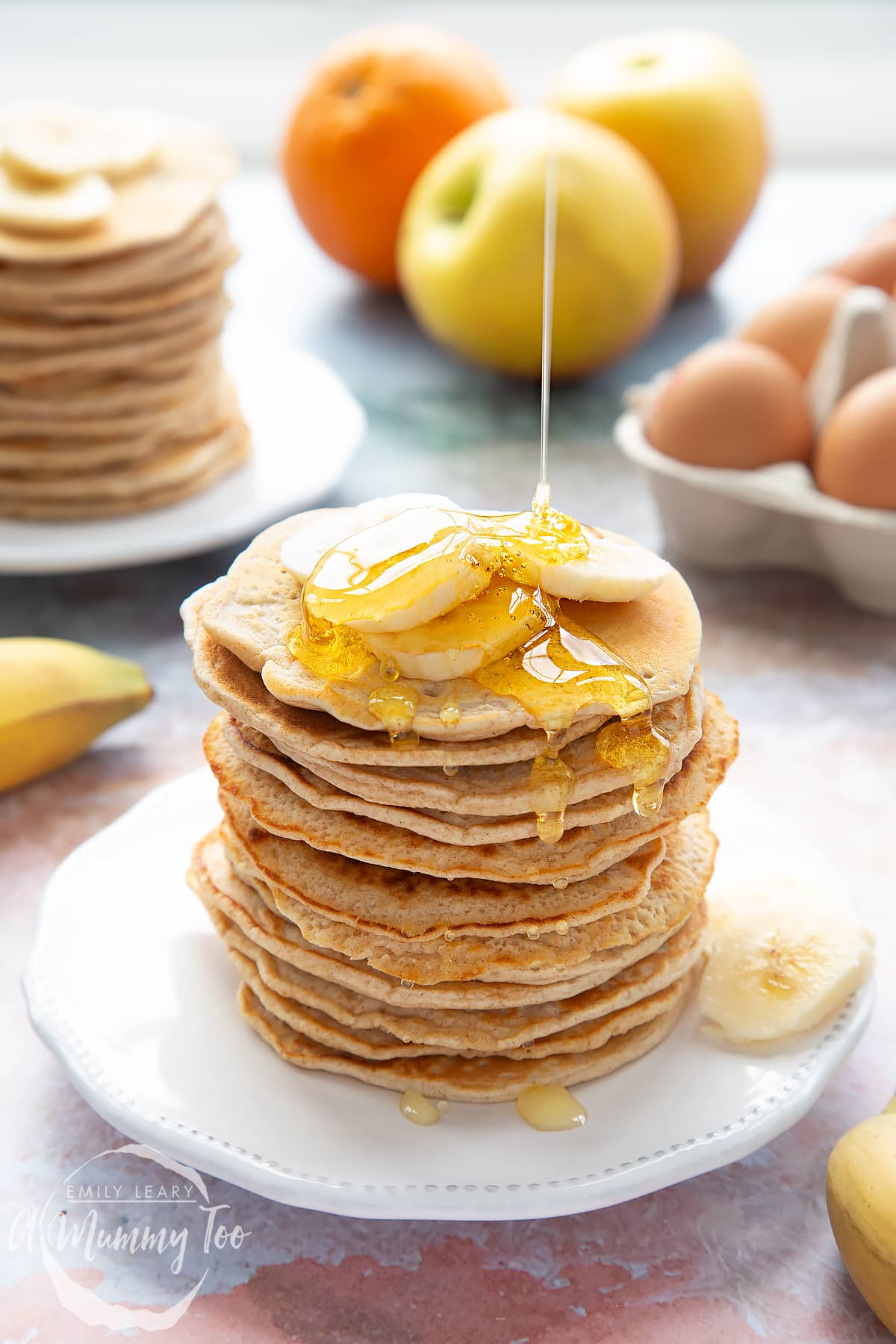 A stack of fluffy pancakes topped with syrup and banana on a white plate