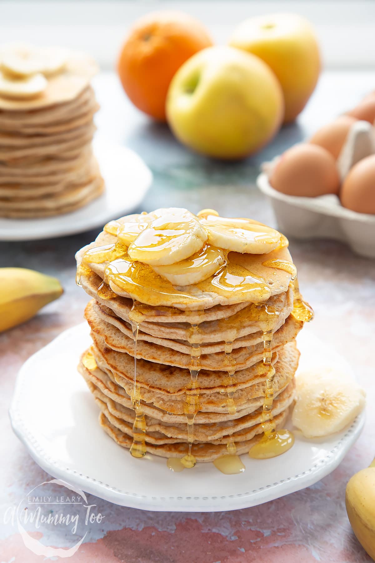 Overhead shot of a pancake stack on a white plate topped with banana and syrup with the A Mummy Too logo in the corner