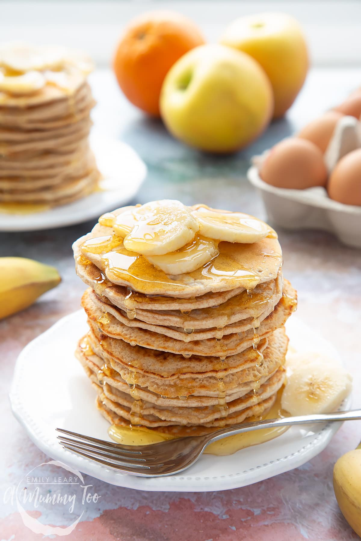 A stack of fluffy pancakes topped with syrup and banana on a white plate and fork