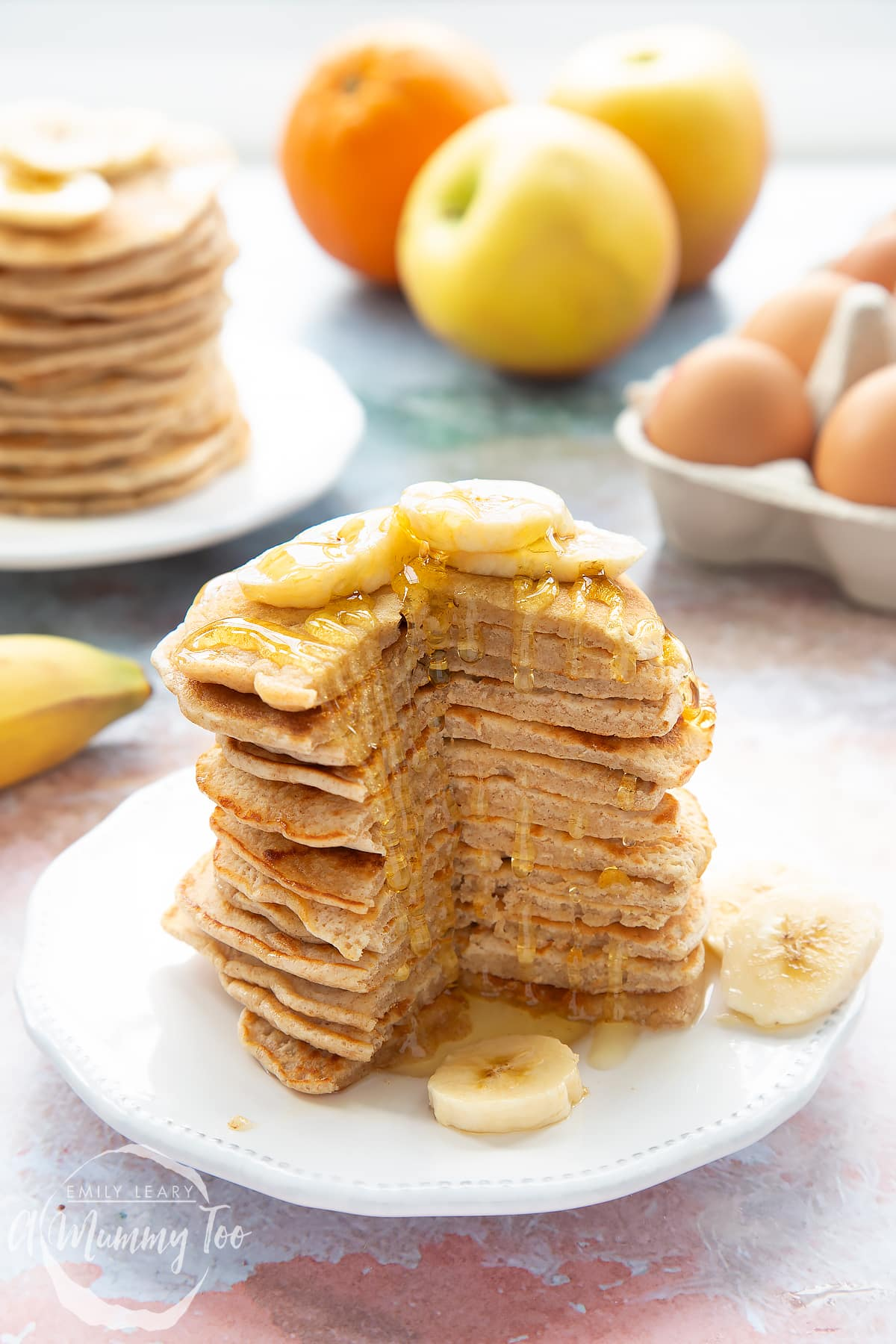 A stack of fluffy pancakes with a cut out of the front topped with syrup and banana on a white plate