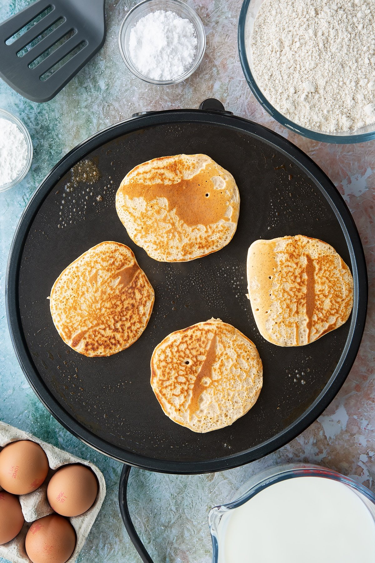 Overhead shot of a hot plate cooking four pancakes cooking
