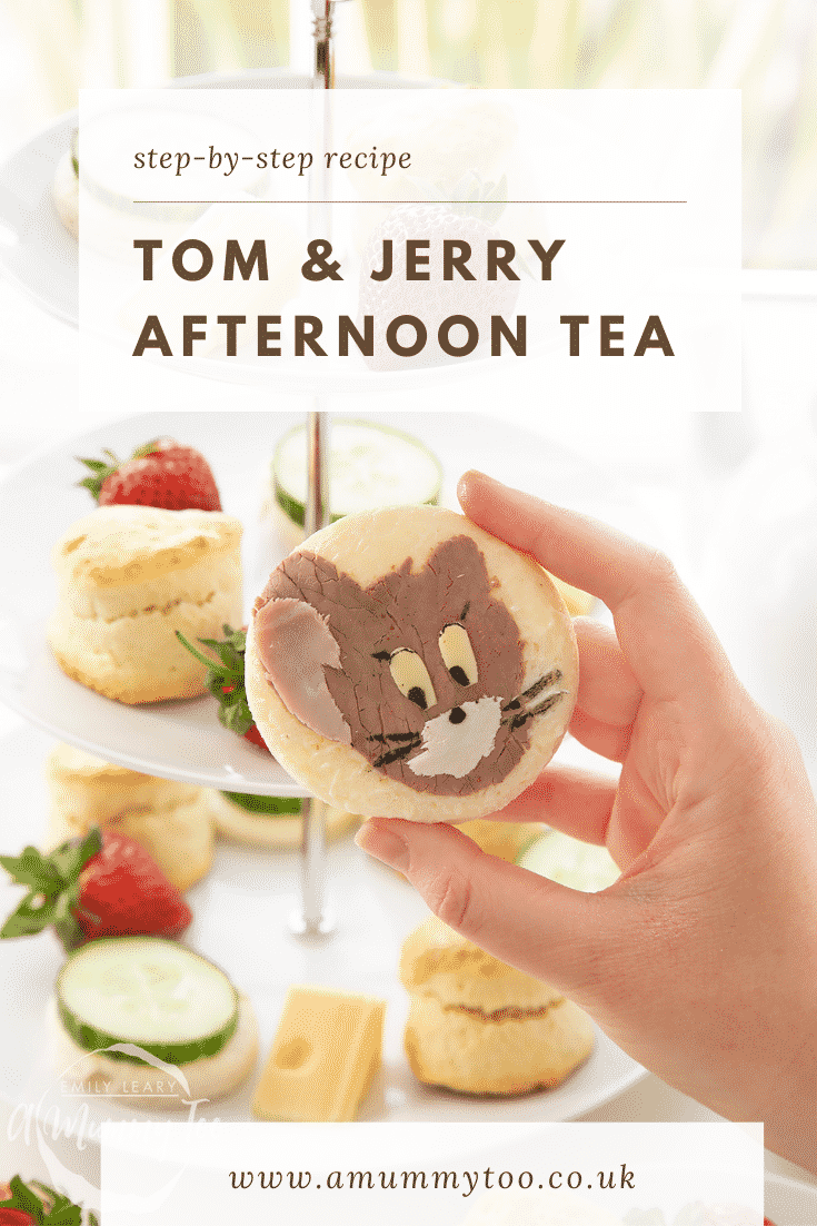 Hand holding a Tom and Jerry sandwhich with a three tier cake stand in the background.