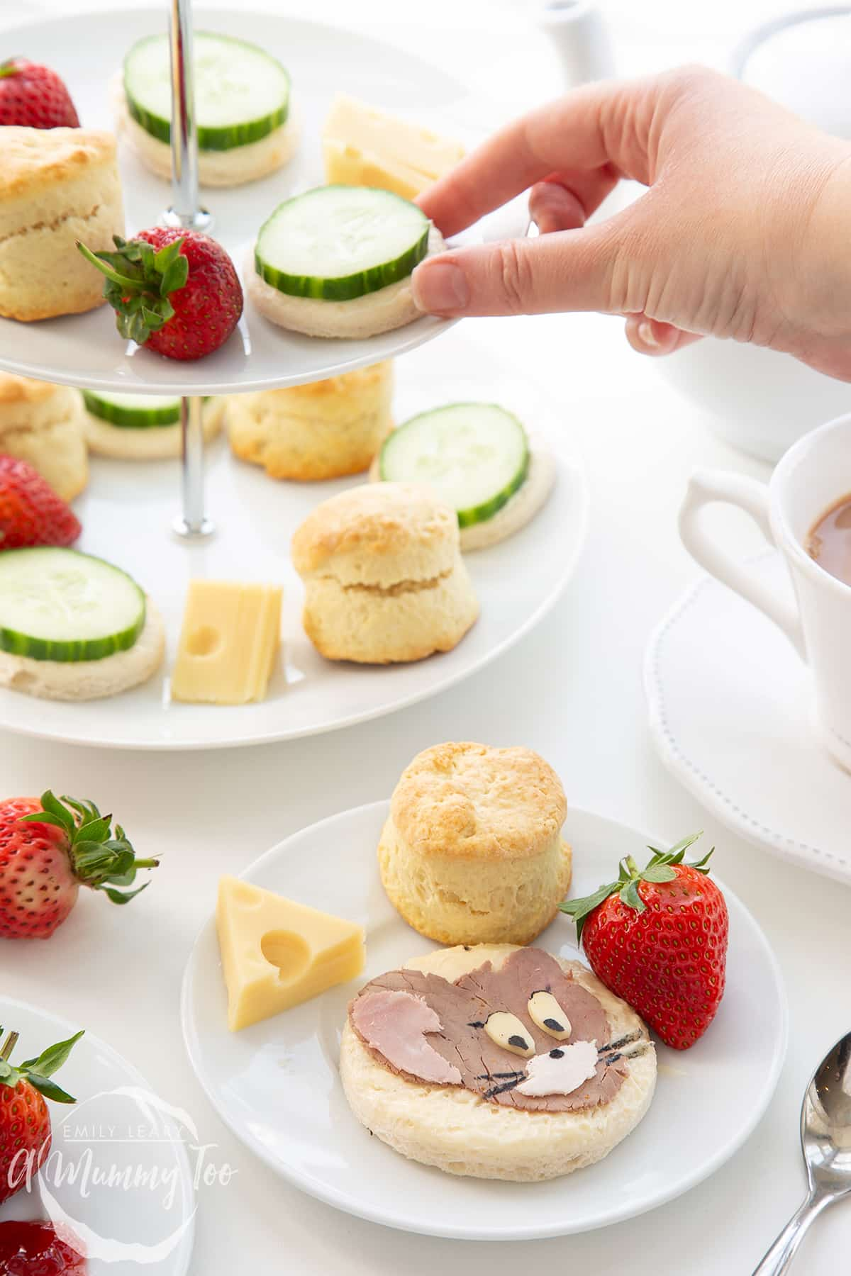 Tom and Jerry afternoon tea on a cake stand with a combination of scones, sandwhiches, cheese and strawberries.