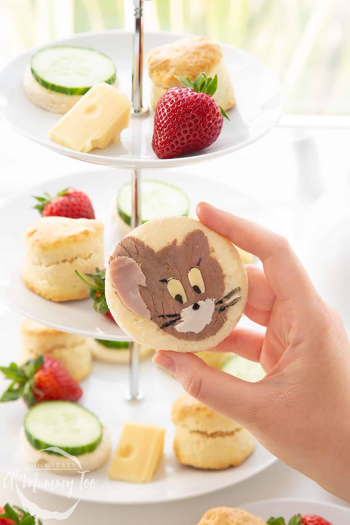 Hand holding up one of the Tom and Jerry sandwhiches with a cake stand filled with Tom and Jerry afternoon tea essentials in the background.