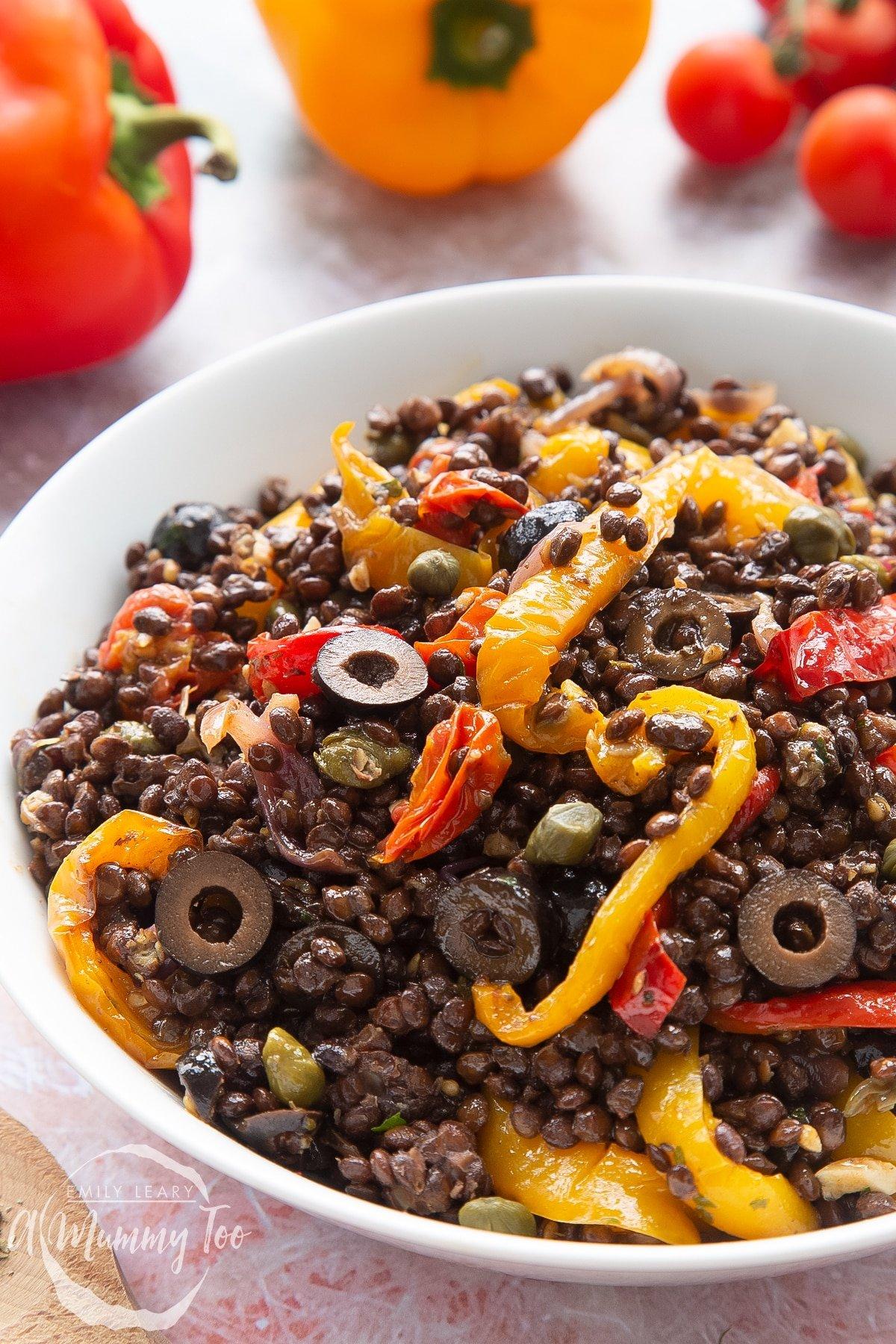Close up of vegan lentil salad served in a white shallow bowl.