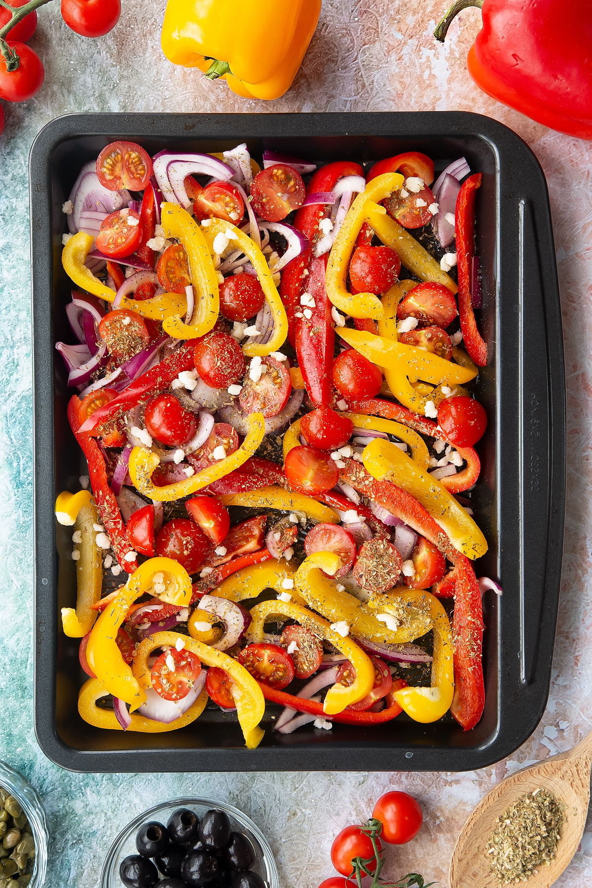 Halved cherry tomatoes, sliced chopped peppers and sliced onions with garlic, olive oil and oregano in an oven tray. Ingredients to make vegan lentil salad surround the tray.