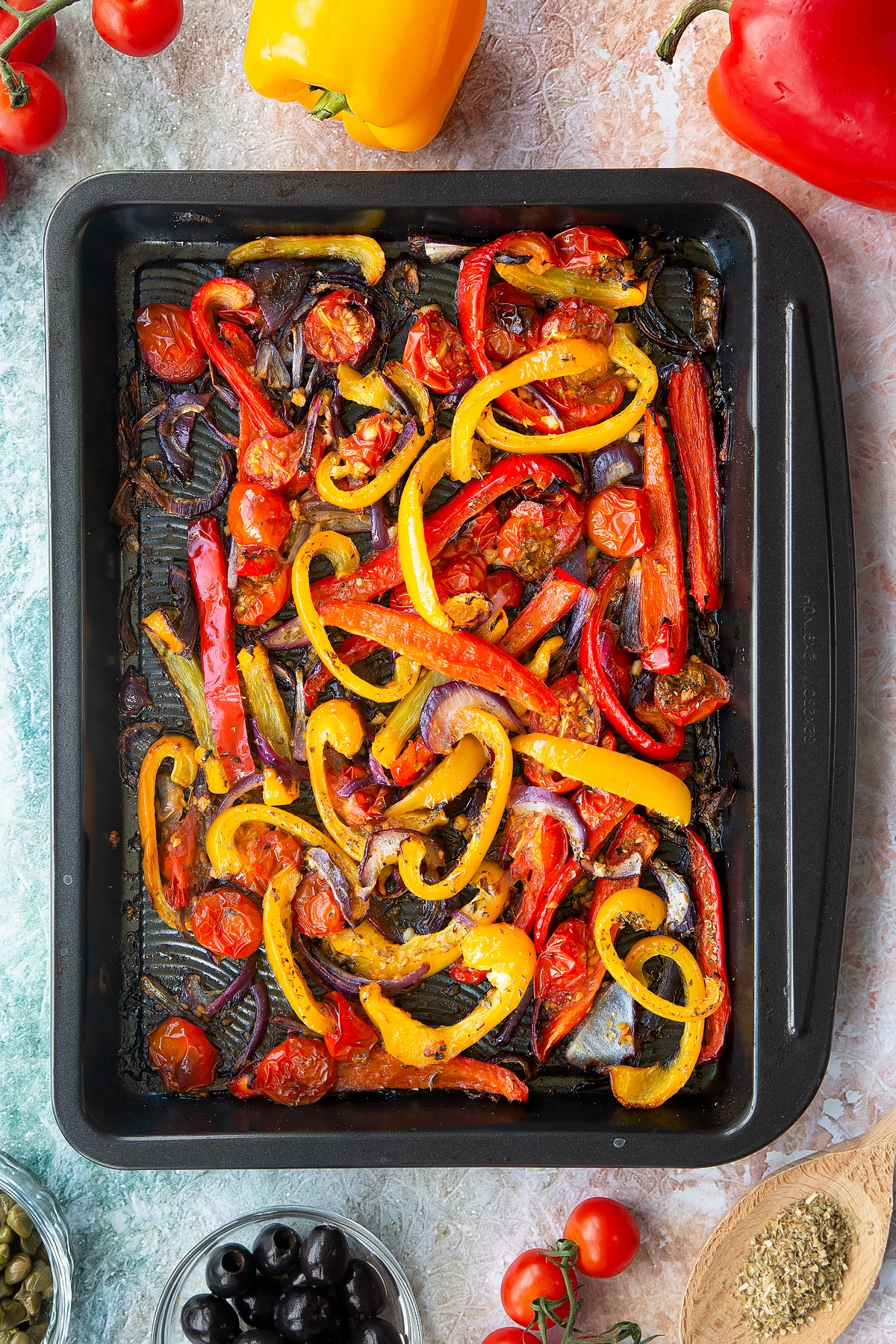 Roasted cherry tomatoes, peppers and onions in an oven tray. Ingredients to make vegan lentil salad surround the tray.