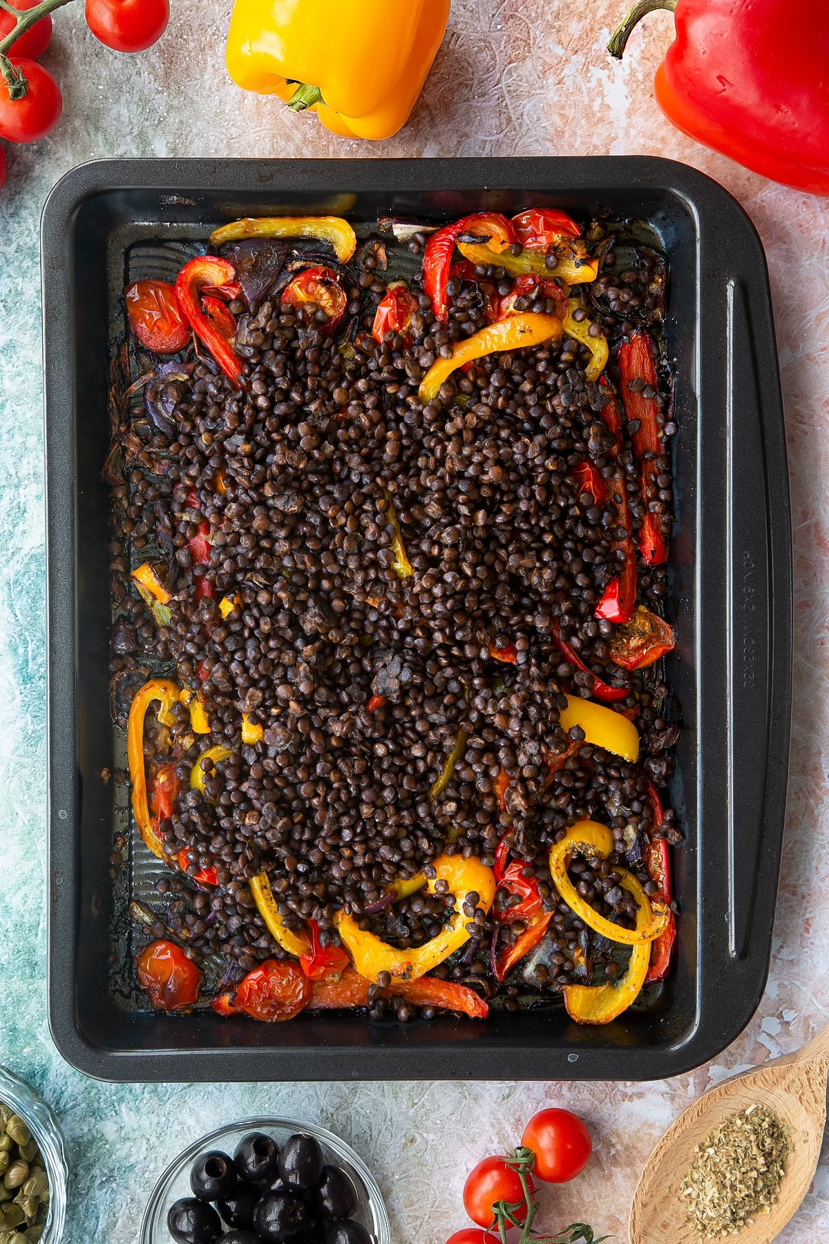 Roasted cherry tomatoes, peppers and onions in an oven tray, topped with cooked puy lentils. Ingredients to make vegan lentil salad surround the tray.