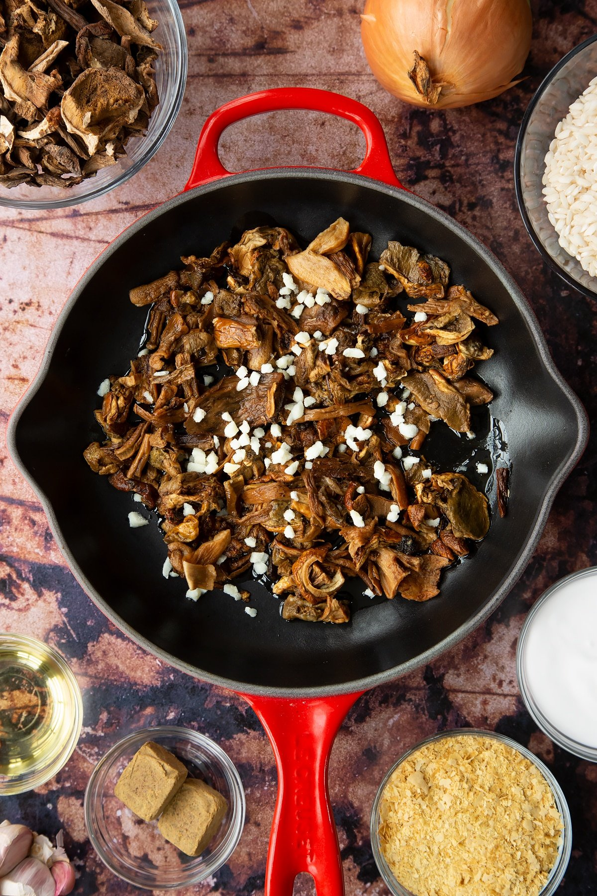 Soaked porcini mushrooms, oil and garlic in a pan. Ingredients to make vegan mushroom risotto surround the pan.