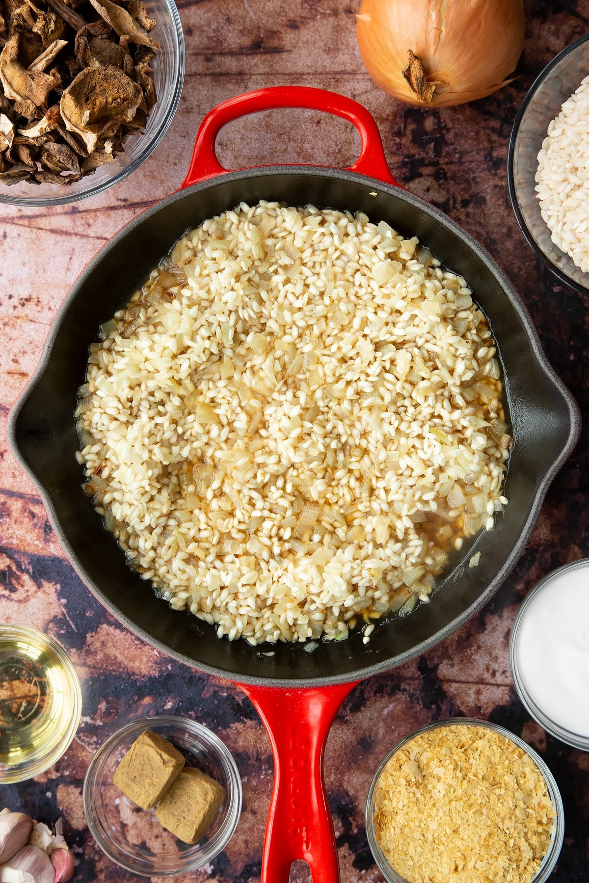 Lightly fried onions and arborio rice covered with a little stock in a pan. Ingredients to make vegan mushroom risotto surround the pan.