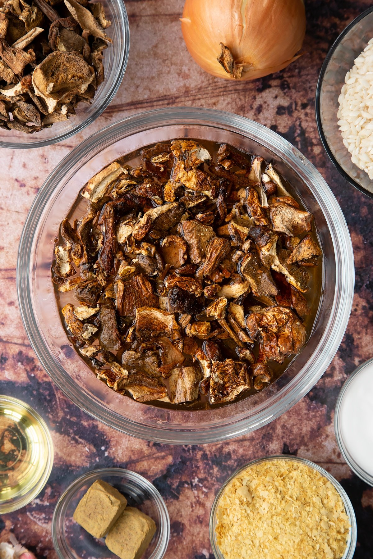 Dried porcini mushrooms covered with water in a glass bowl. Ingredients to make vegan mushroom risotto surround the bowl.