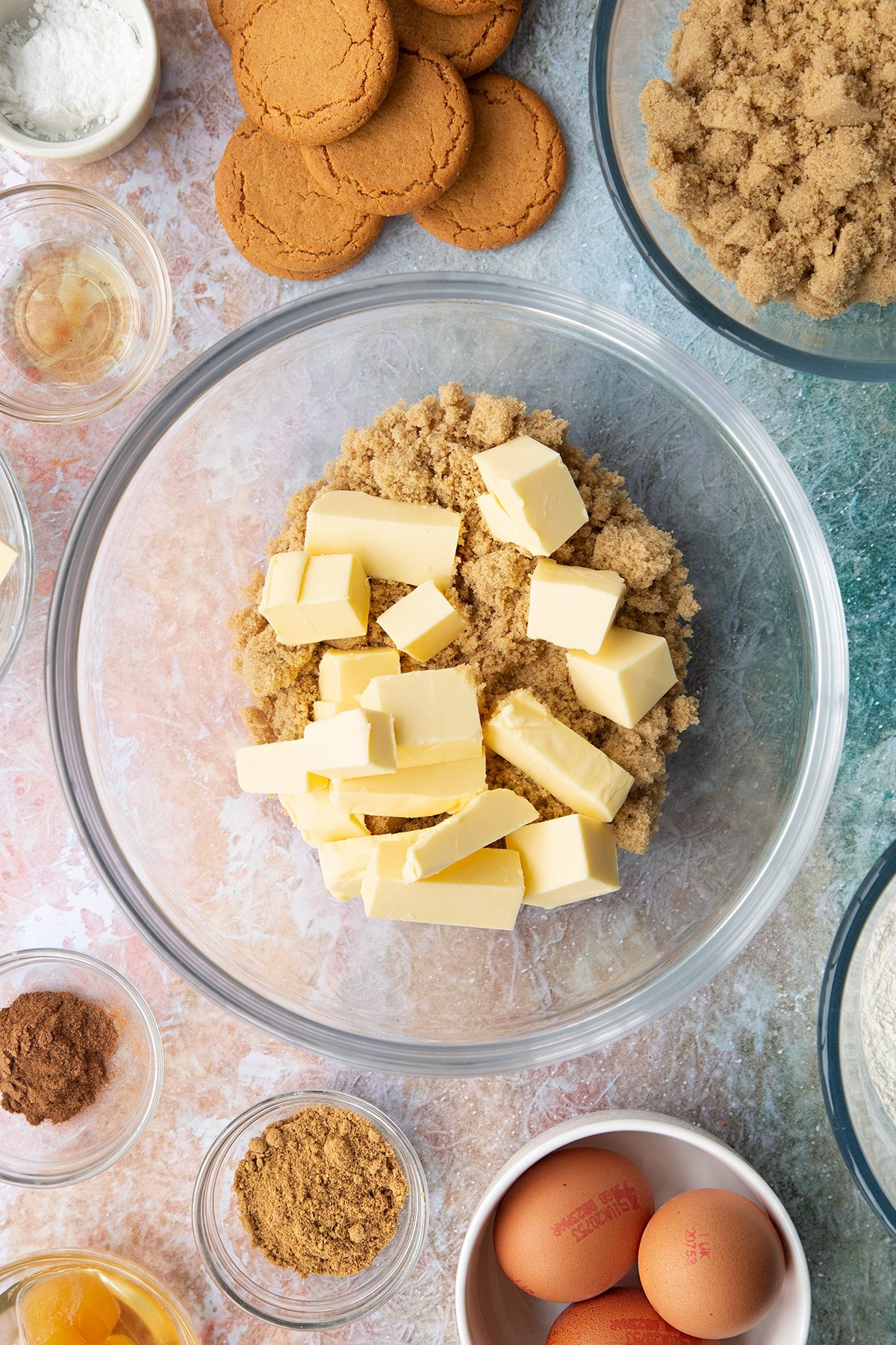 Butter and soft light brown sugar in a mixing bowl. Ingredients to make ginger cupcakes surround the bowl.
