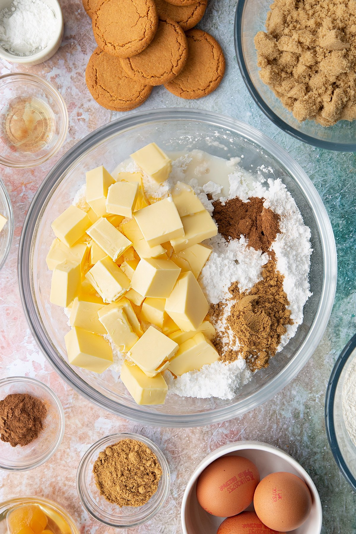 Icing sugar, butter, cinnamon, ginger, vanilla and milk in a large bowl. Ingredients to make ginger cupcakes surround the bowl.