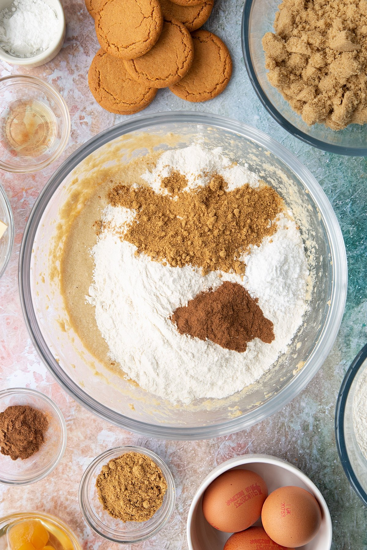 Butter, soft light brown sugar, milk, eggs and vanilla whisked together in a mixing bowl with flour, cinnamon and ginger on top. Ingredients to make ginger cupcakes surround the bowl.