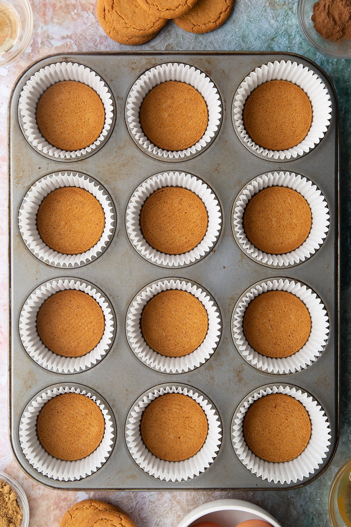 Muffin tin lined with cupcake cases. There's a gingernut biscuit in the base of each case. Ingredients to make ginger cupcakes surround the tin.