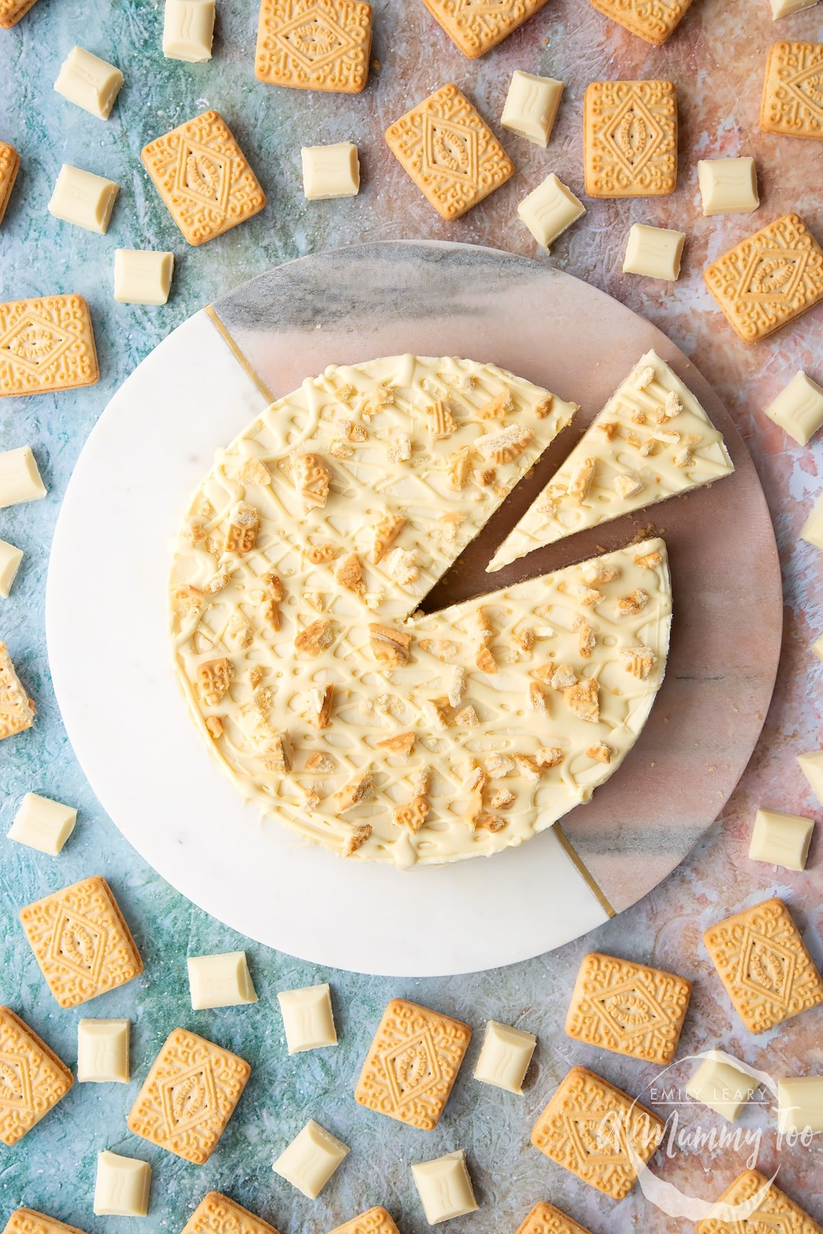 Overhead shot of a cheesecake with a slice cut out surrounded by Custard Cream Biscuits