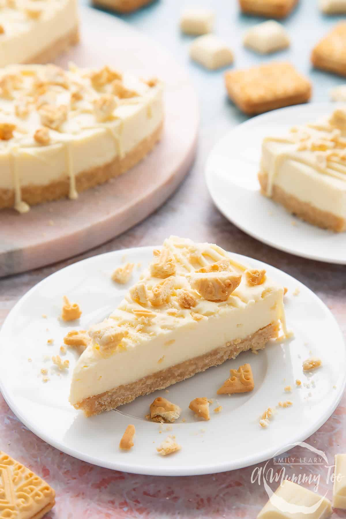 Front view shot of a piece of white chocolate cheesecake toppedw ith custard cream biscuit crumbs on a white plate