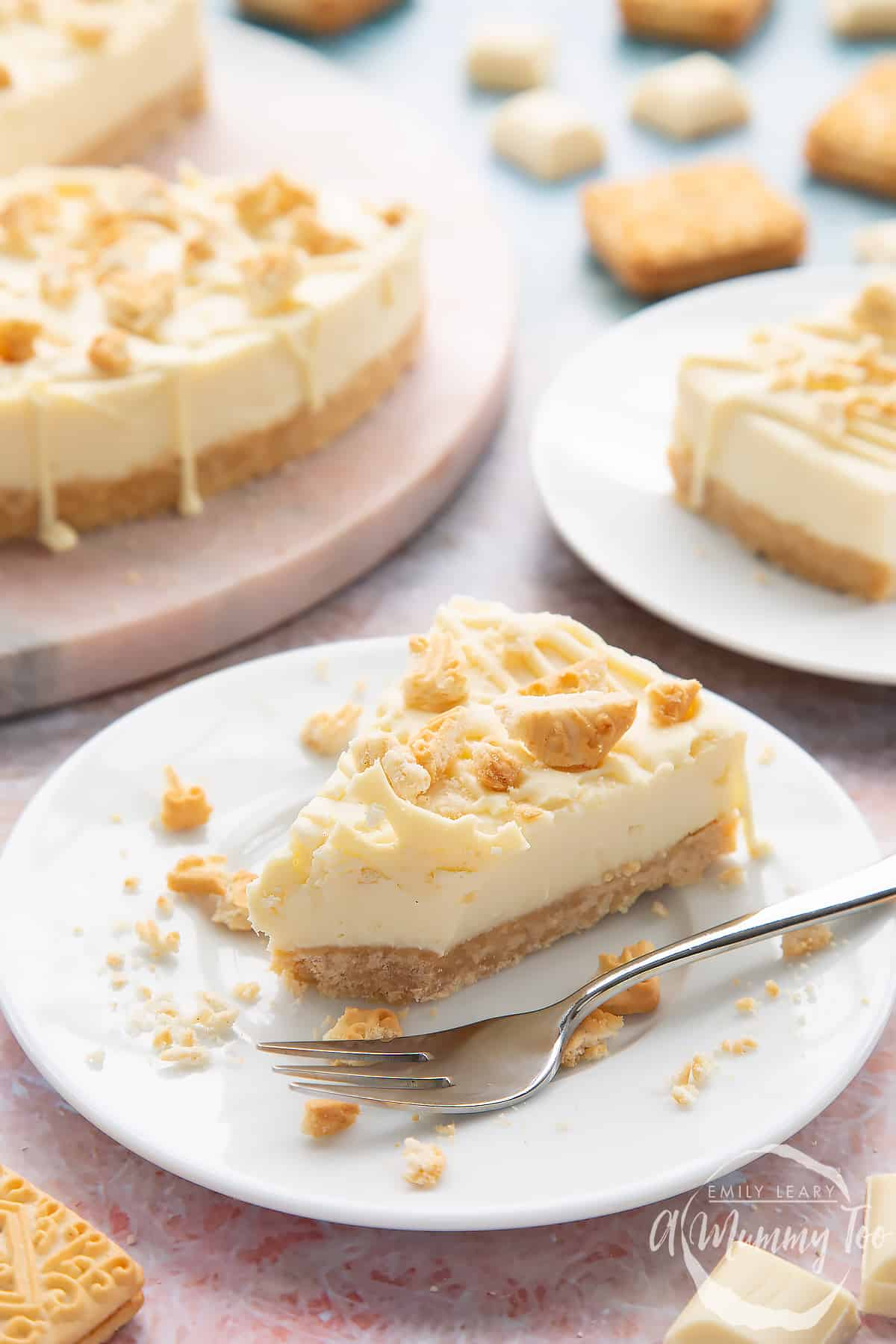 Front view shot of white chocolate cheesecake on a white plate with a fork